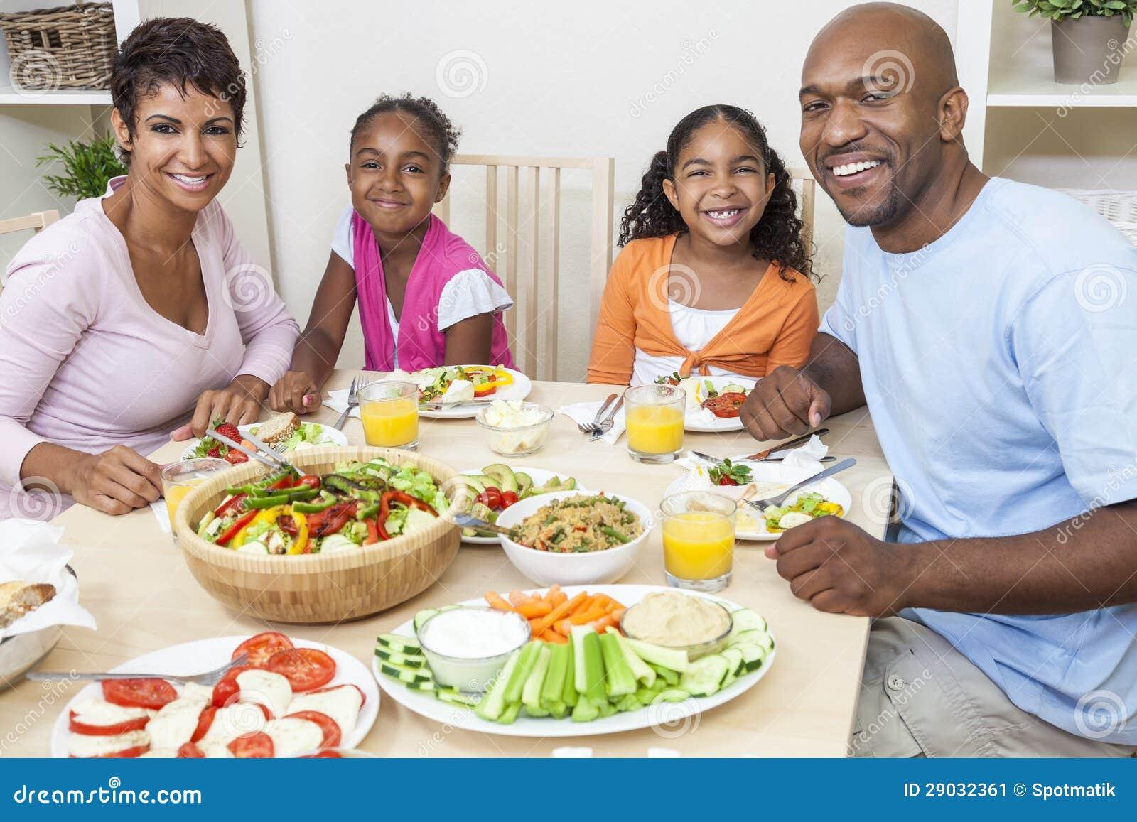 Afrikansk amerikan uppfostrar barn som familjen som äter på att äta middag, bordlägger