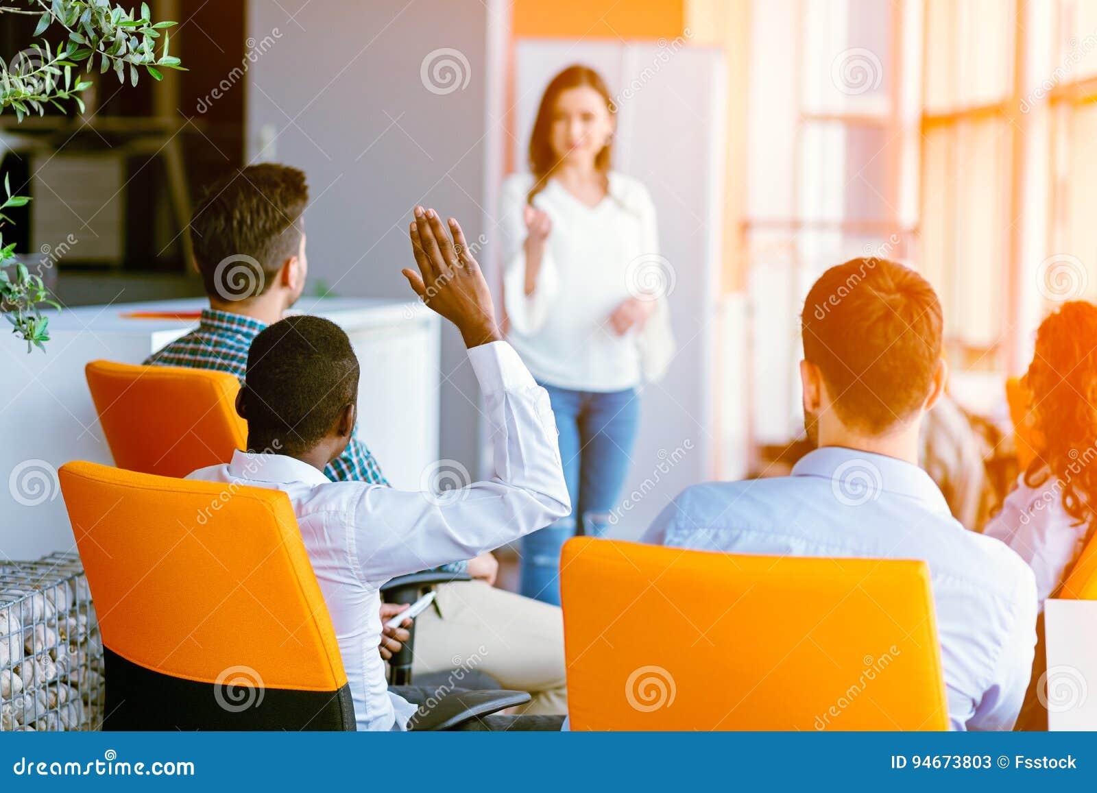 Afrikansk amerikanaffärsfolk som där upp lyfter handen på en konferens för att svara en fråga