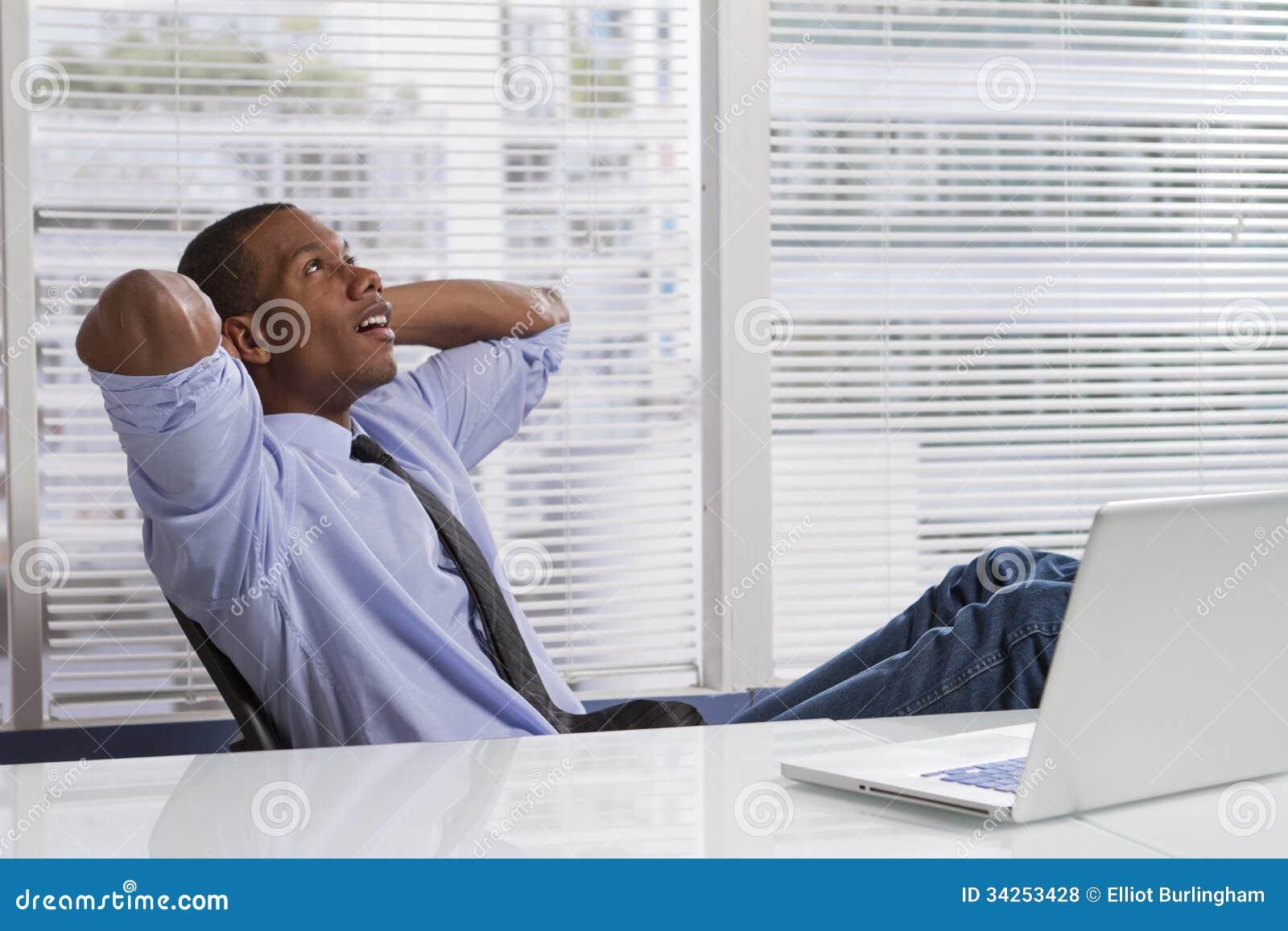 Afrikansk amerikanaffärsman som kopplar av på skrivbordet som är horisontal