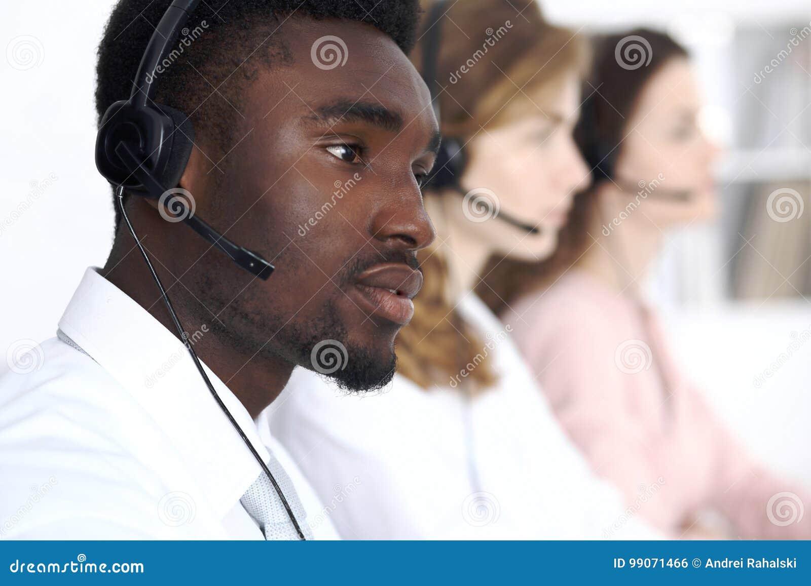 Afrikansk amerikanappelloperatör i hörlurar med mikrofon Affär för appellmitt eller kundtjänstbegrepp