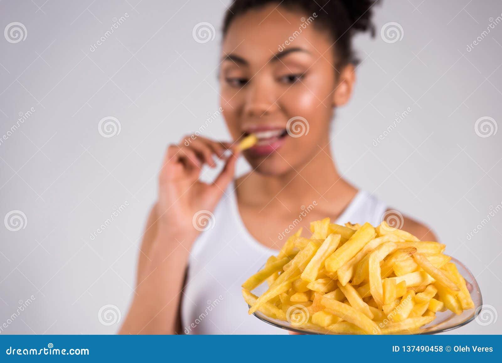 Afrikansk amerikanflicka som äter småfiskar