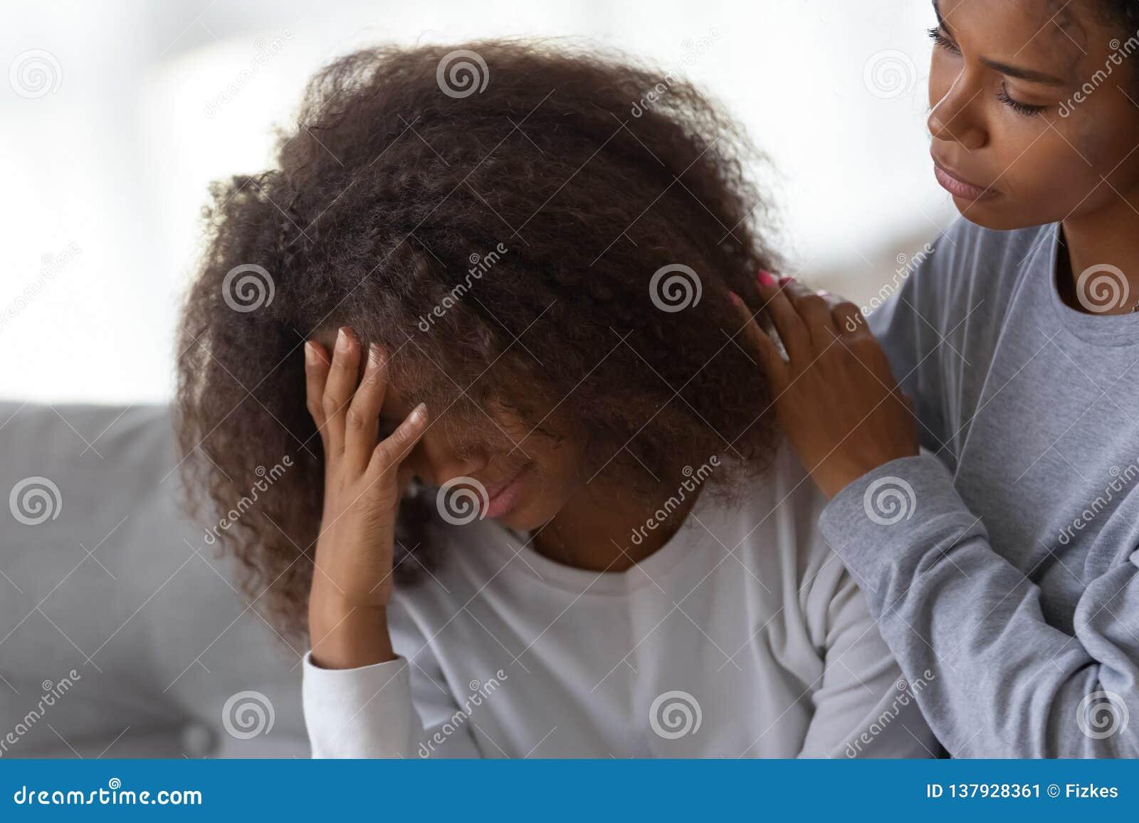 Afrikansk amerikanmammakram som tröstar den ledsna tonårs- dottern
