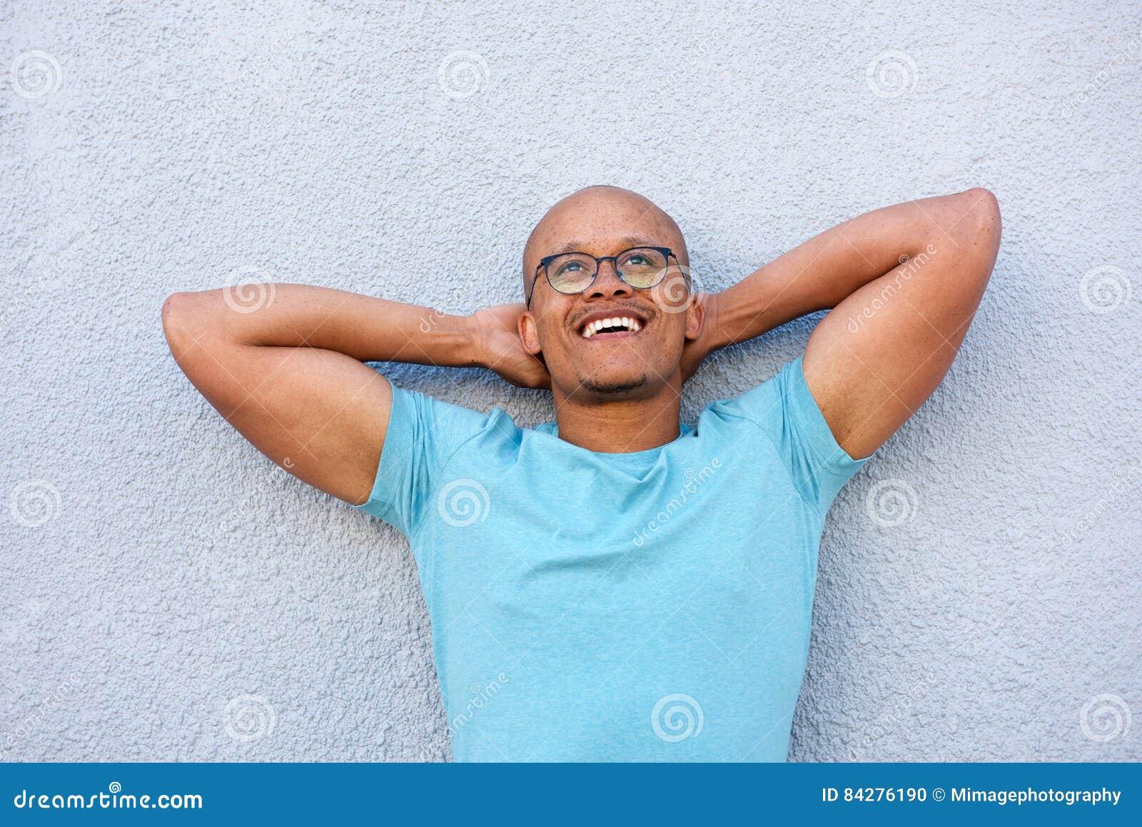 Afrikansk amerikanman som ler med exponeringsglas som ser upp i begrundande