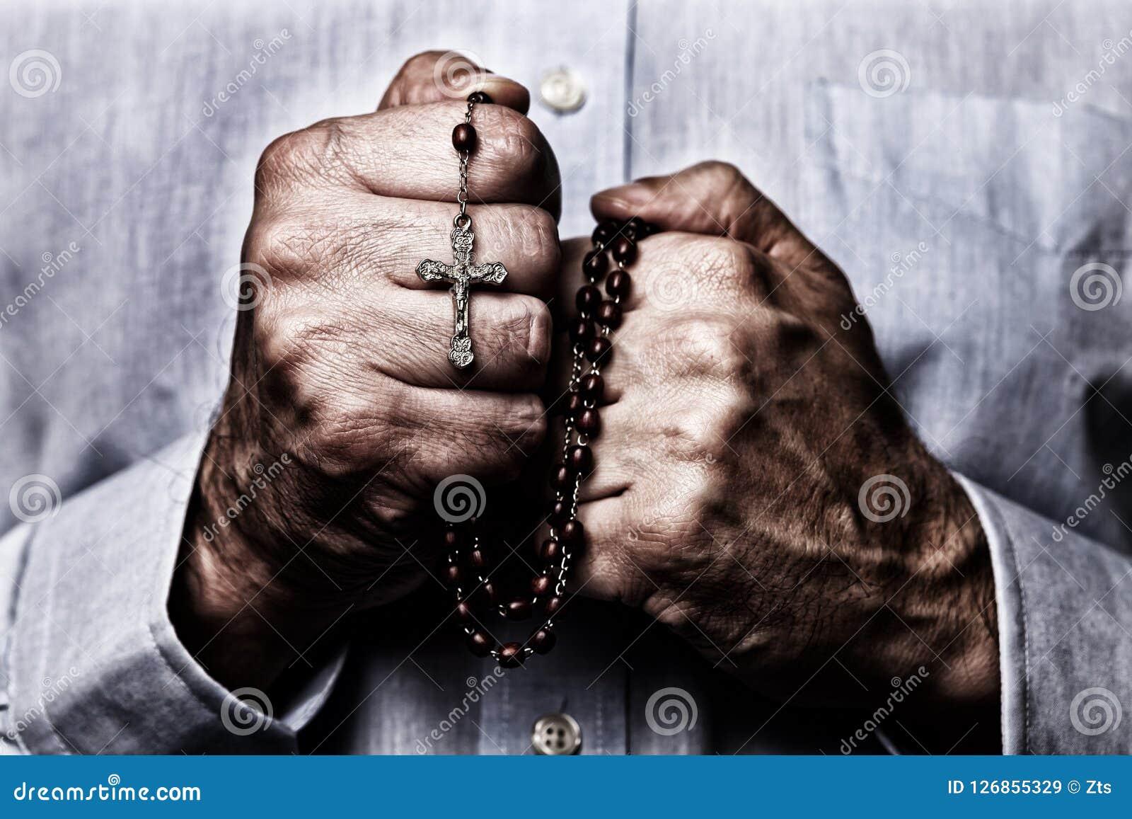 Afrikansk amerikanmannen räcker att be rymma en pärlradband med Jesus Christ i korset eller korset