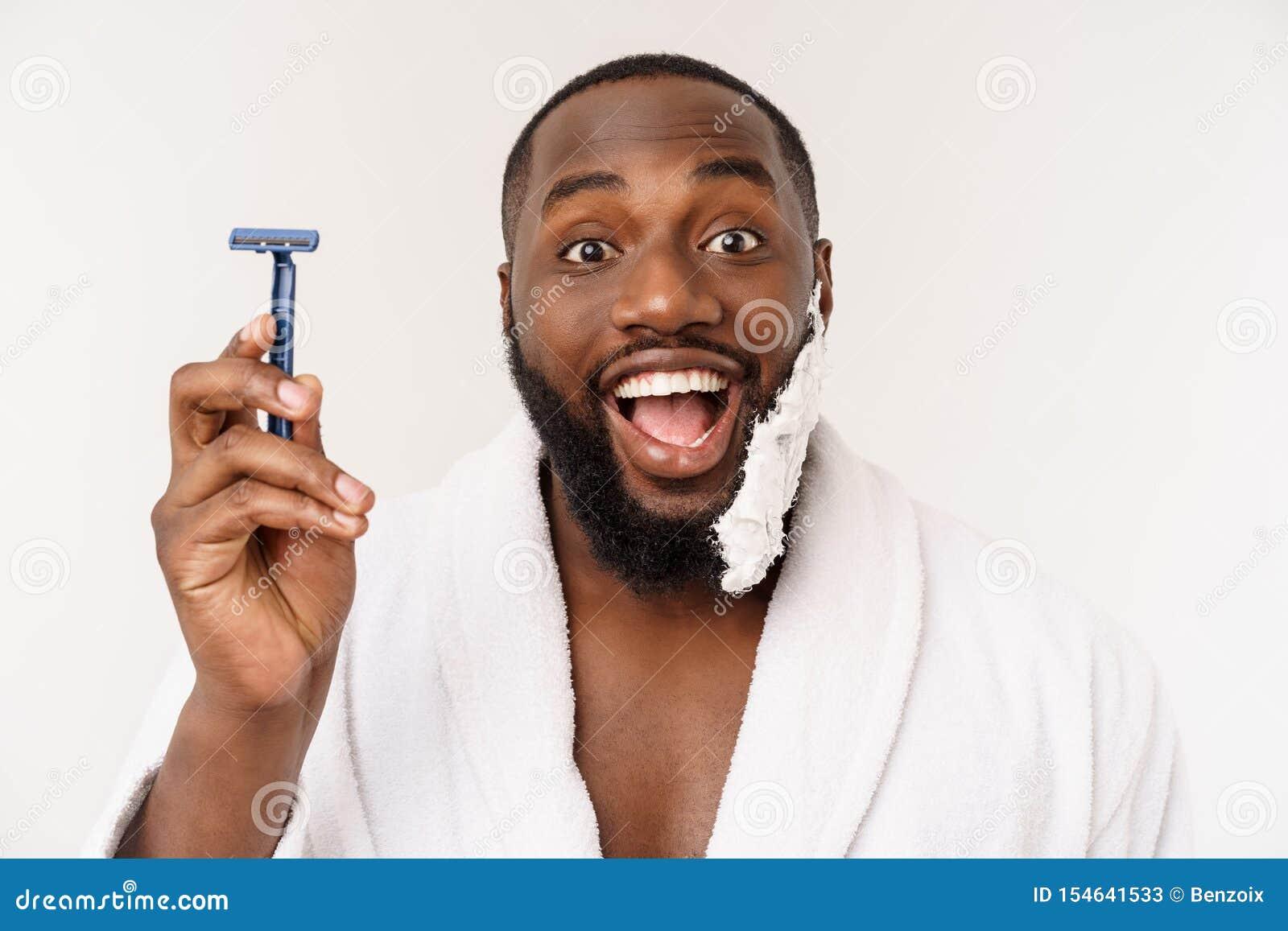 Afrikansk amerikanmannen suddar att raka kr?m p? framsida, genom att raka borsten Male hygien bakgrund isolerad white studio