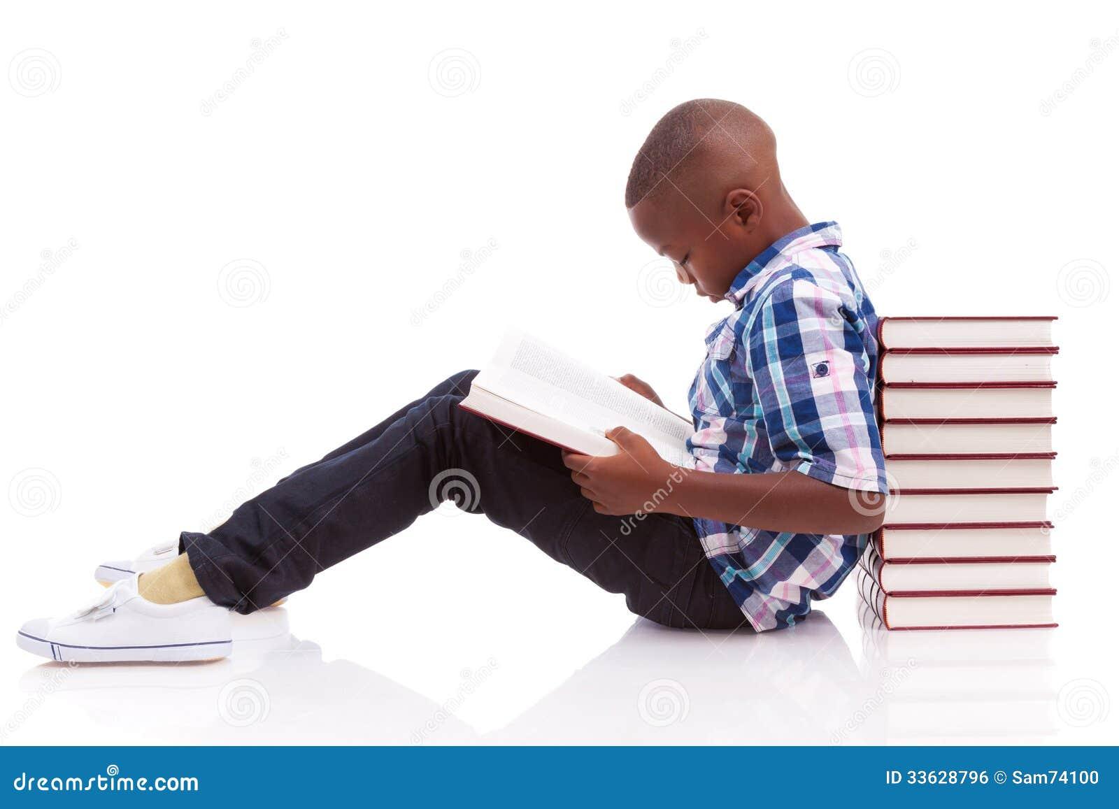 Afrikansk amerikanskolapojke som läser en bok - svarta människor