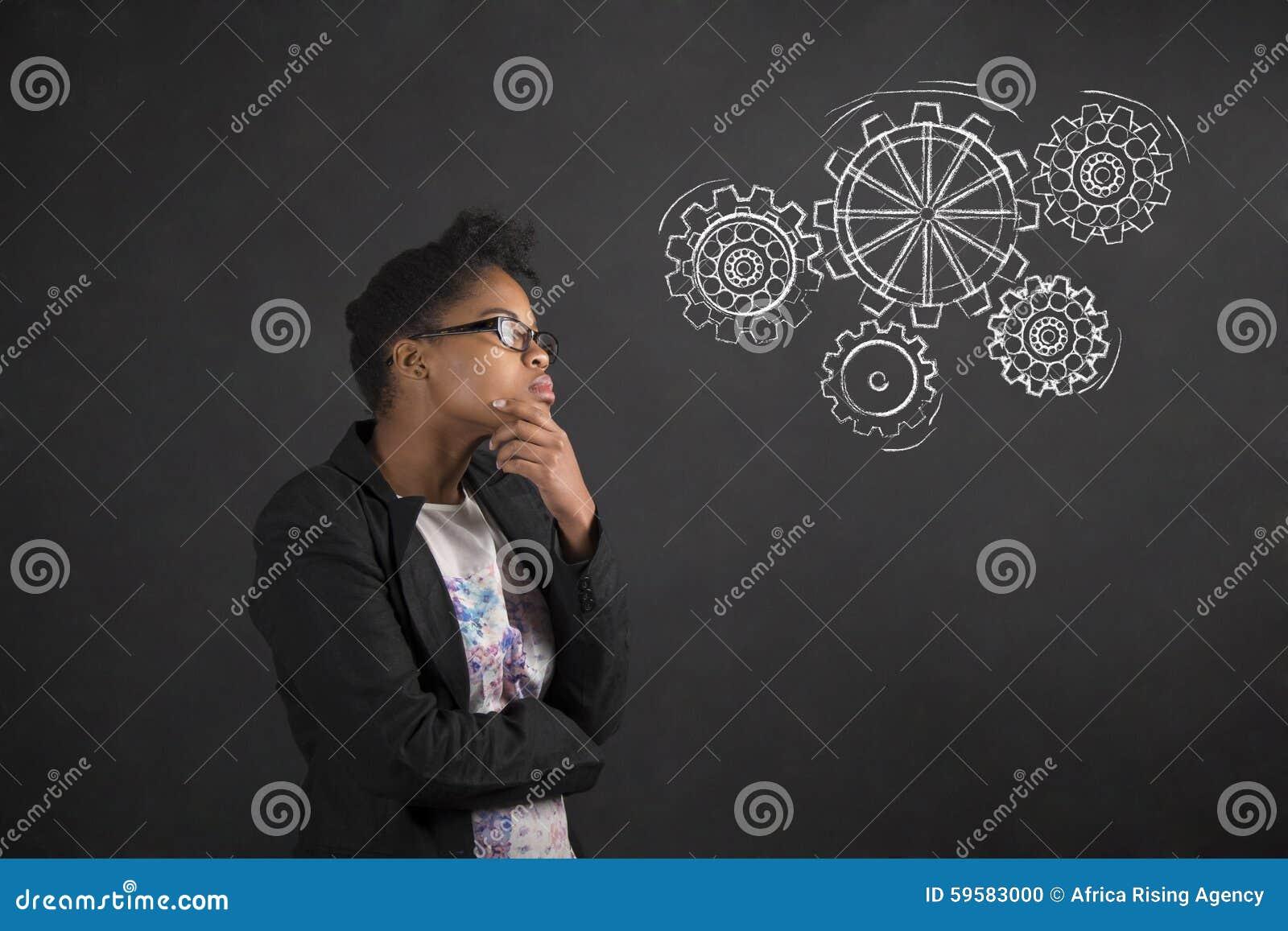 Afrikansk kvinna med handen på hakan som tänker med kugghjul på svart tavlabakgrund