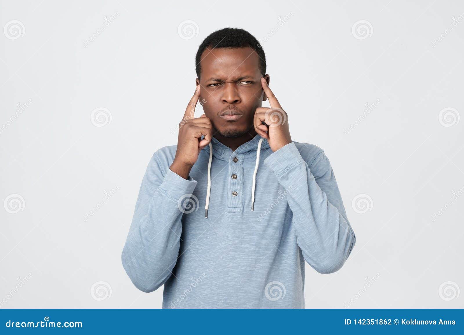 Afrikanska amerikanen som mannen håller fingrar på tempel, väljer den bästa passande lösningen