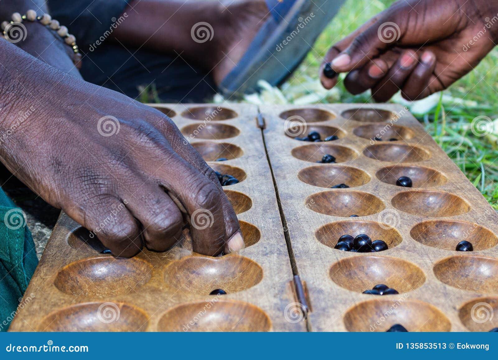 Afrikanska män som spelar en lokal brädelek
