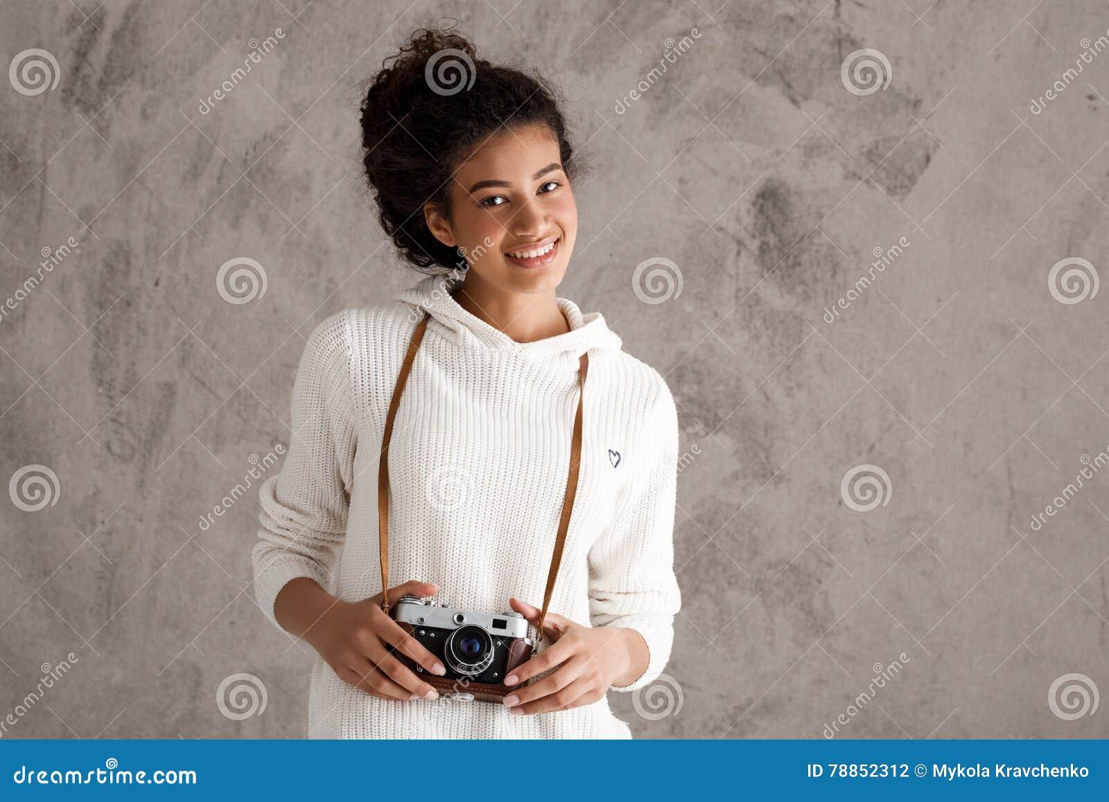 Afrikanskt kvinnligt le för fotografi som rymmer kameran över beige bakgrund