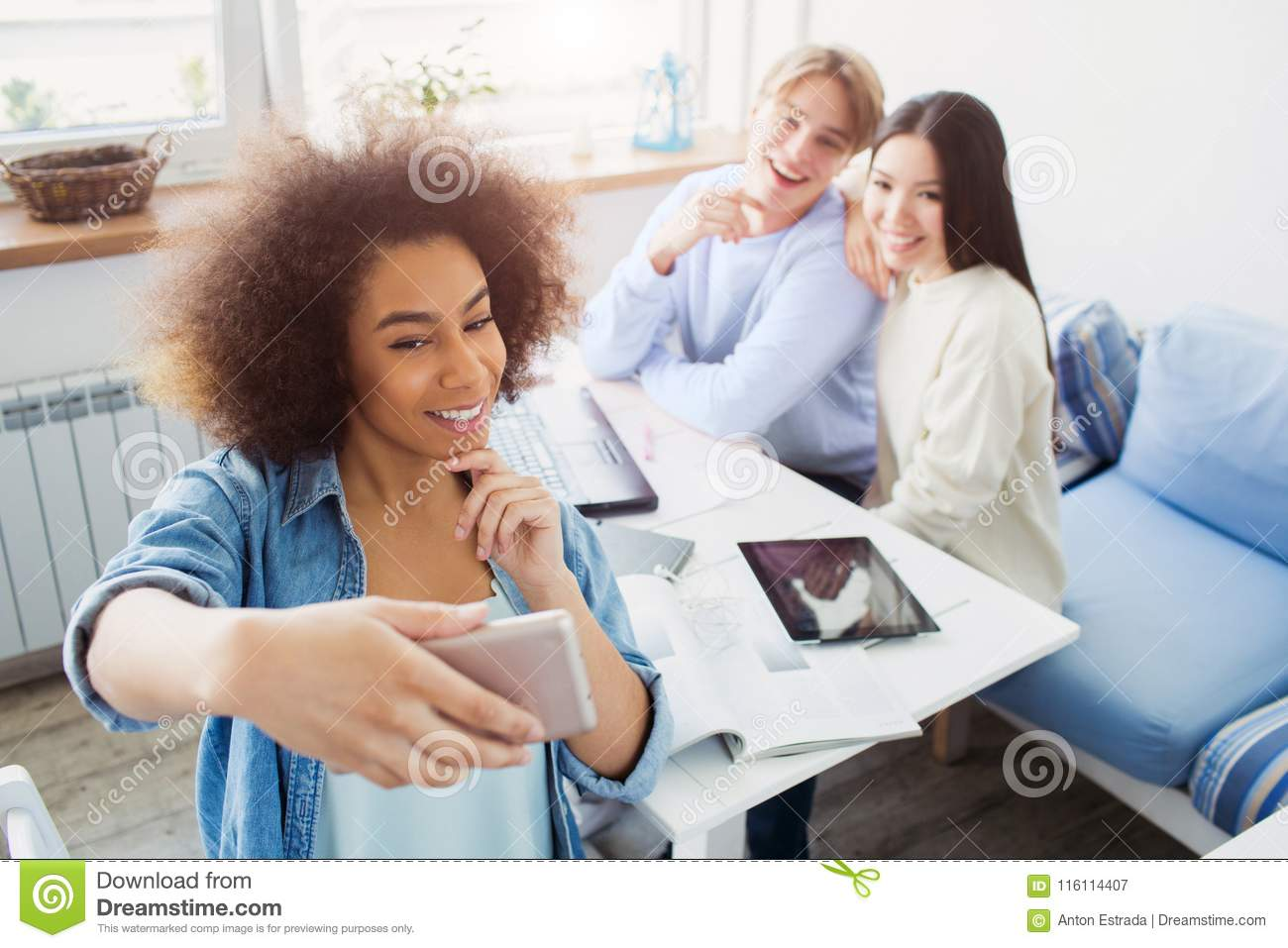 Afro american girl is taking a selfie of herself and her friends which are sitting at the table. All of them are posing