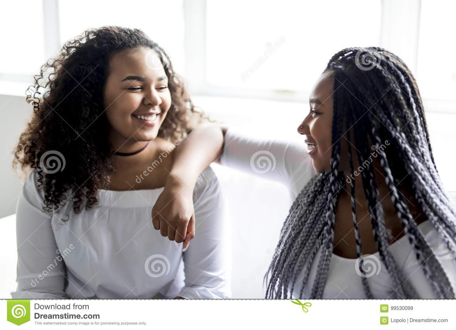 Afro amerikanskt sammanträde för tillgivna vänner på soffan
