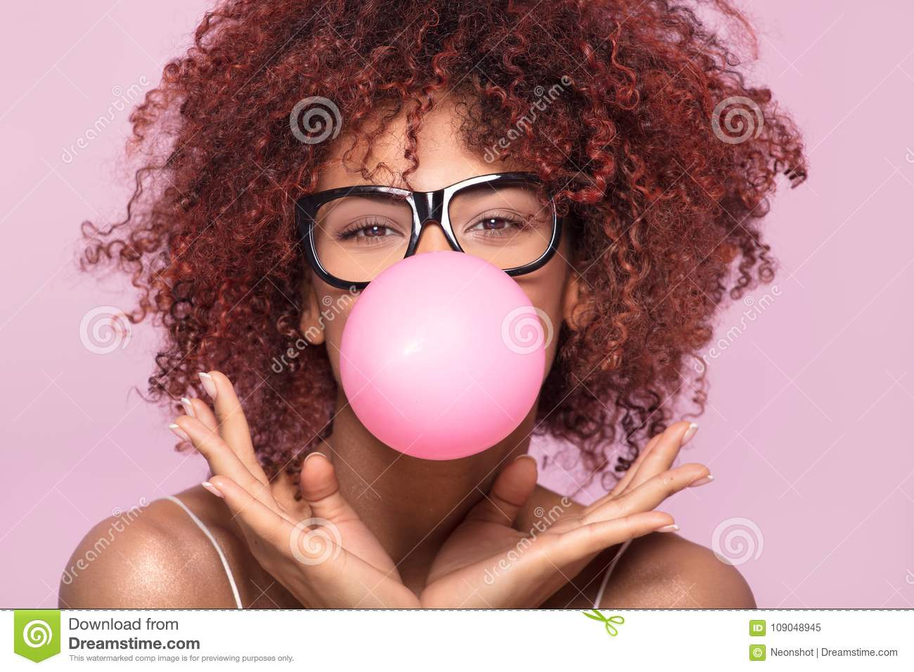 Afro girl blowing bubble gum balloon.