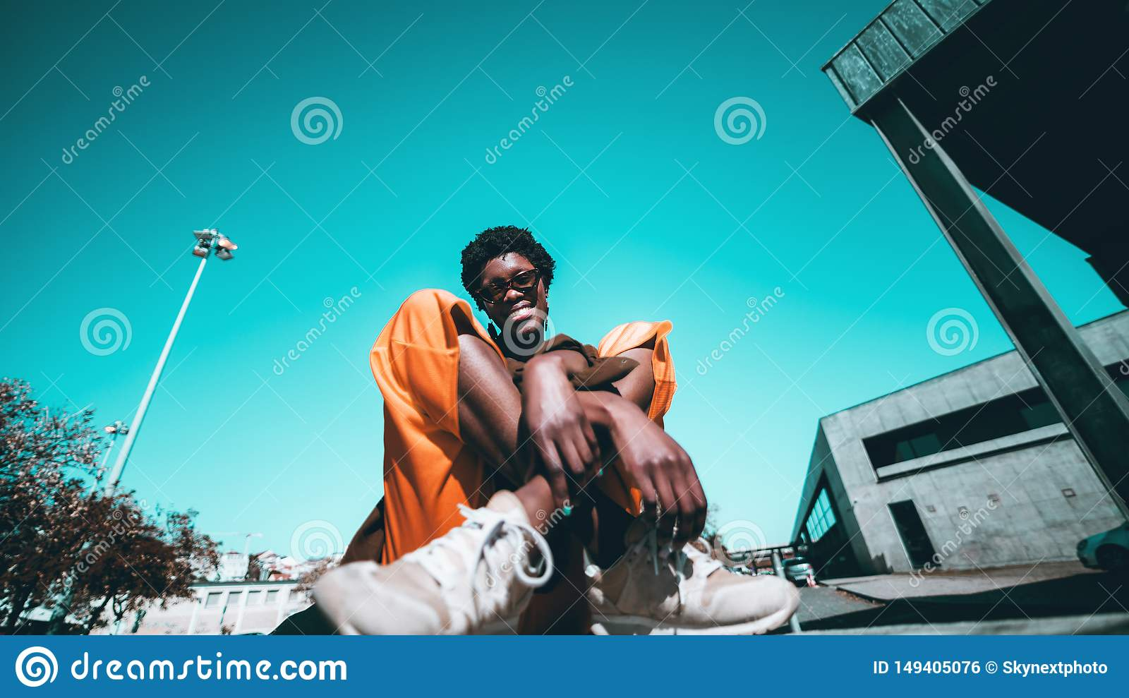 An Afro girl is sitting on the ground