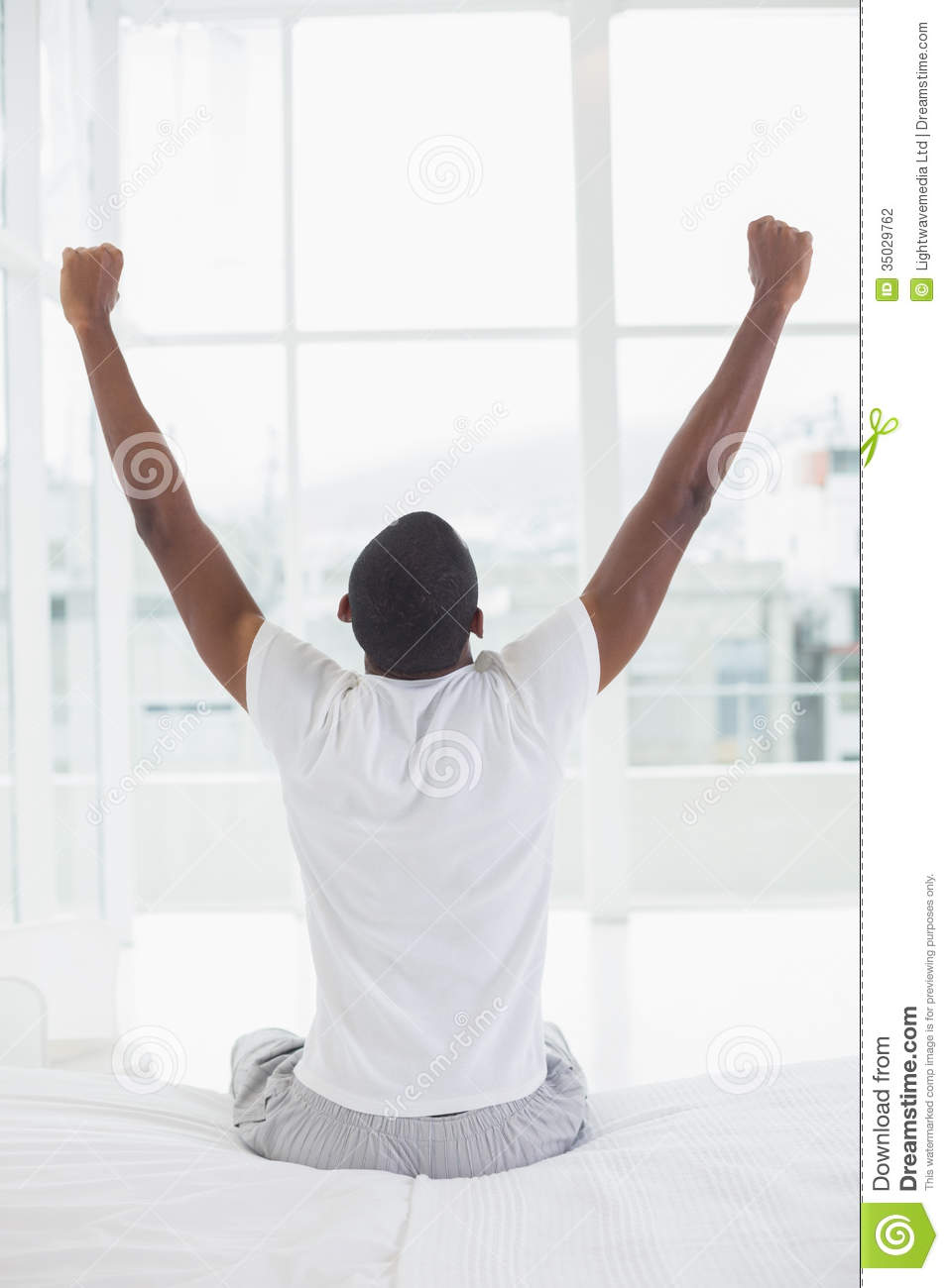 Afro Man Waking Up In Bed And Stretching His Arms Stock