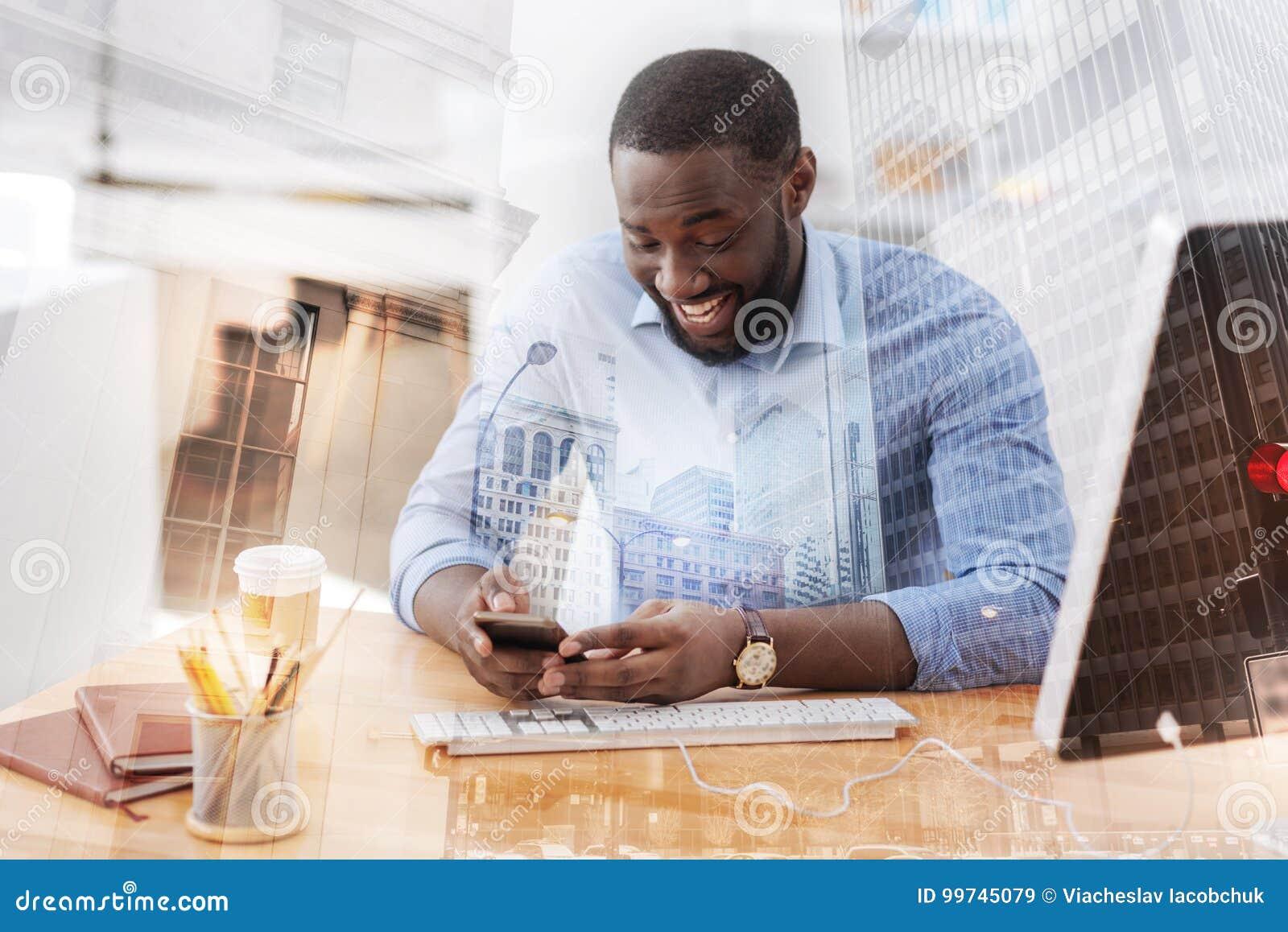 Afroamericano emocionado que usa el teléfono móvil
