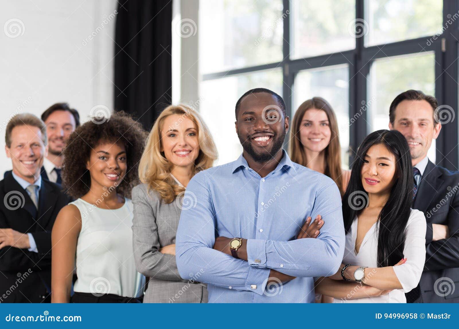 Afroamerikaner-Geschäftsmann-Chef-With Group Of-Geschäftsleute im kreativen Büro, erfolgreiche Mischungs-Rennmann-Führung
