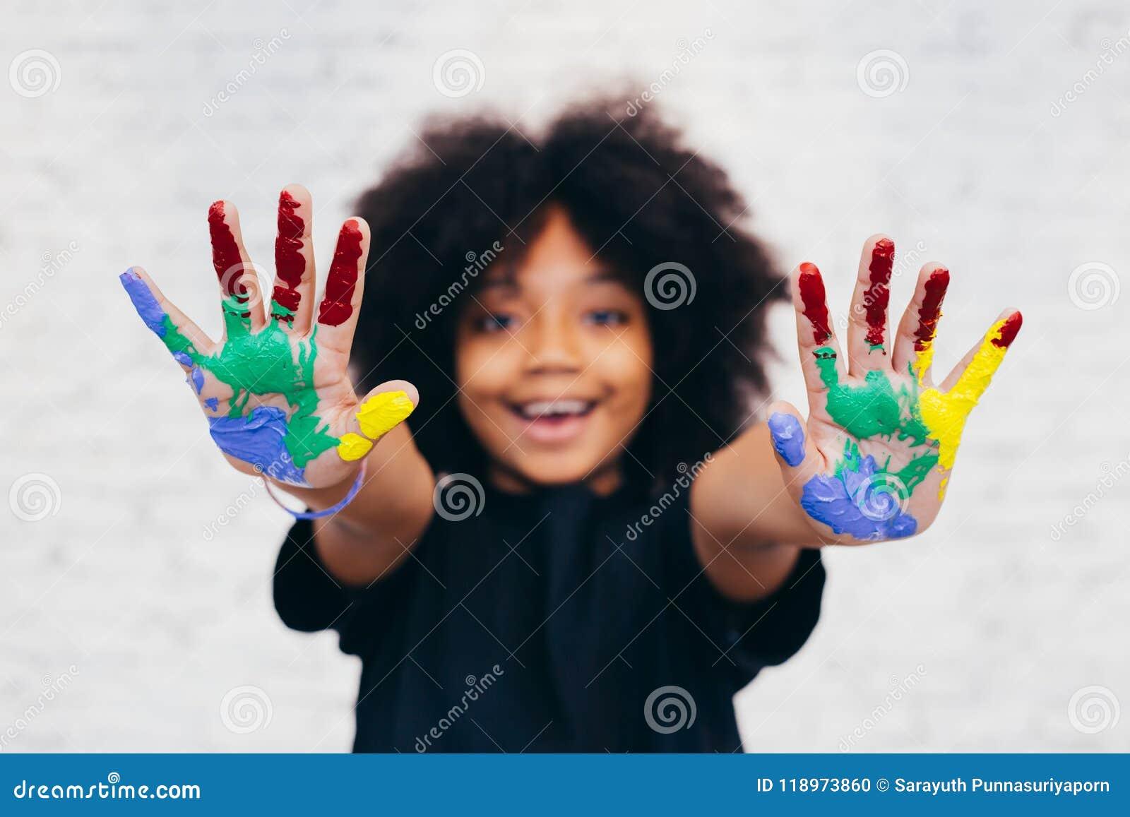 Afroamerikaner spielerisch und kreatives Kind, das Hände schmutzig mit vielen Farben erhält