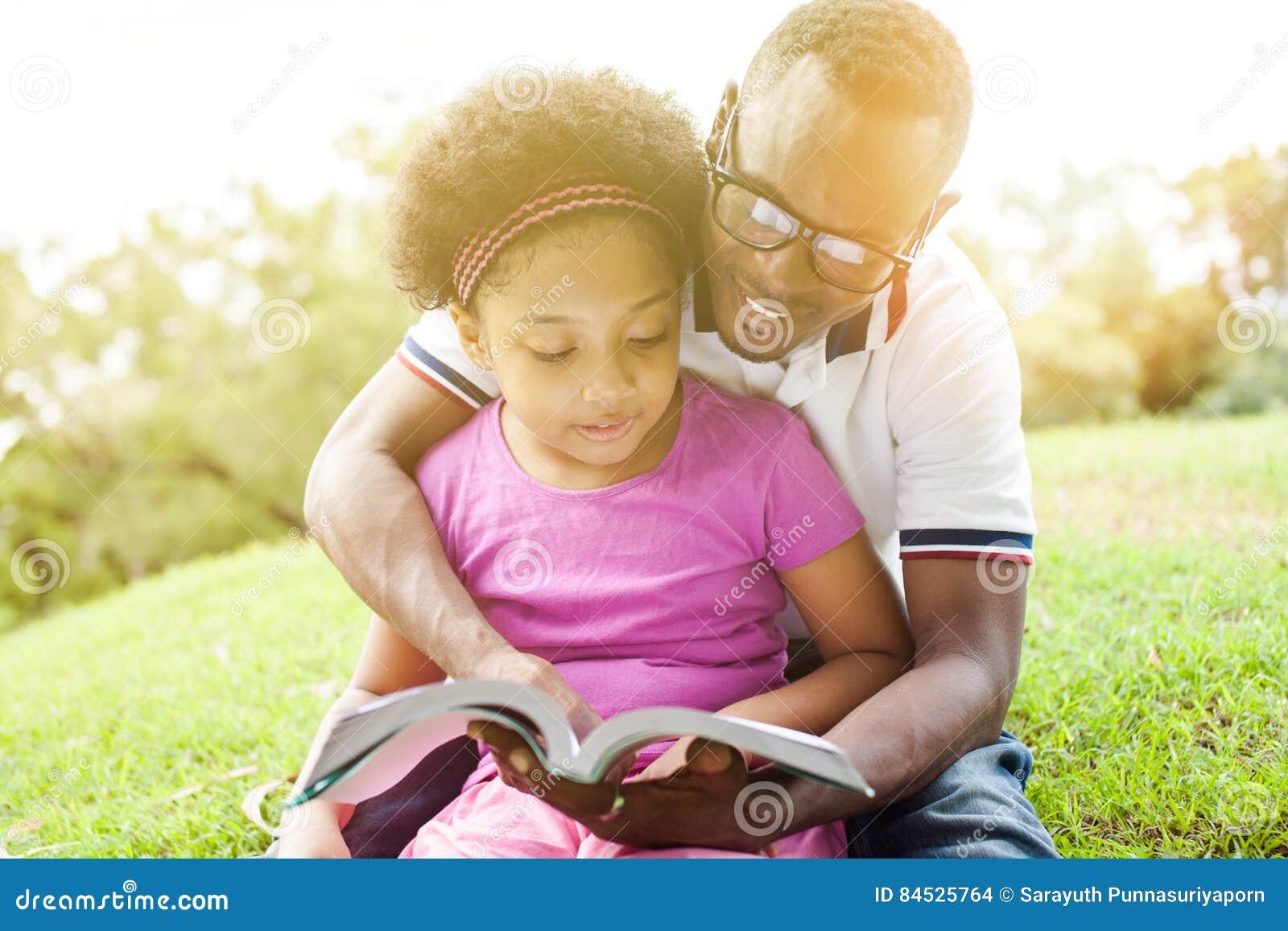 Afroamerikanerfamilie, die zusammen ein Buch im Park im Freien liest