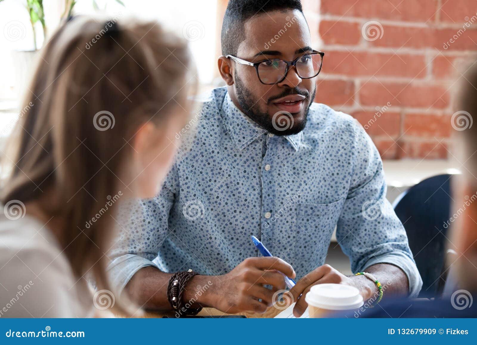 Afroamerikanergeschäftsmann, der mit Kollegen an der Anweisung spricht