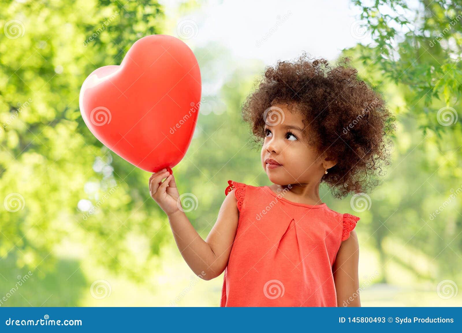 Afroamerikanerm?dchen mit geformtem Ballon des Herzens