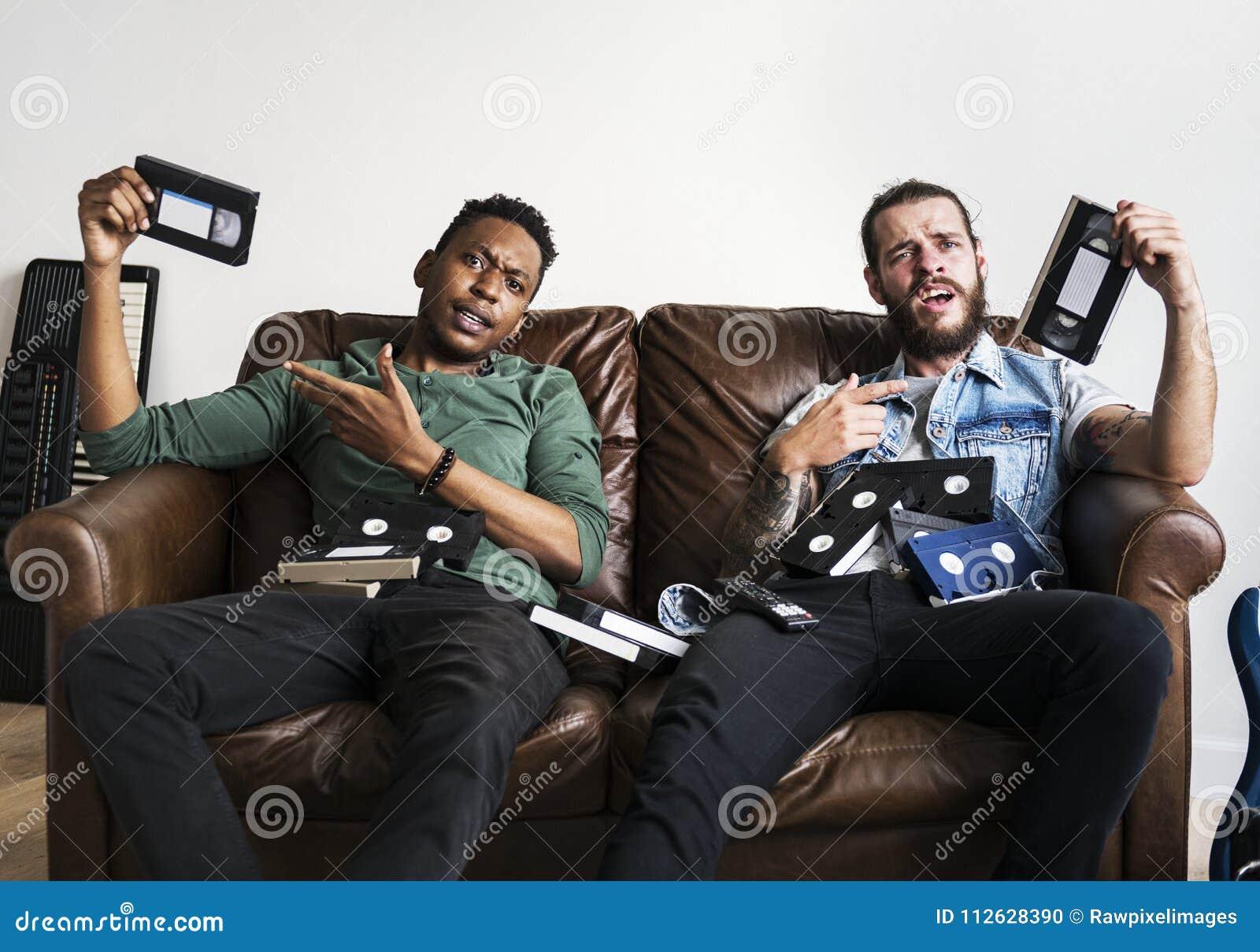 Afroamerikanermann und männliche Hippies eines Kaukasiers, die Videoband Weinlese VHSs halten und dumme Gesichter machen