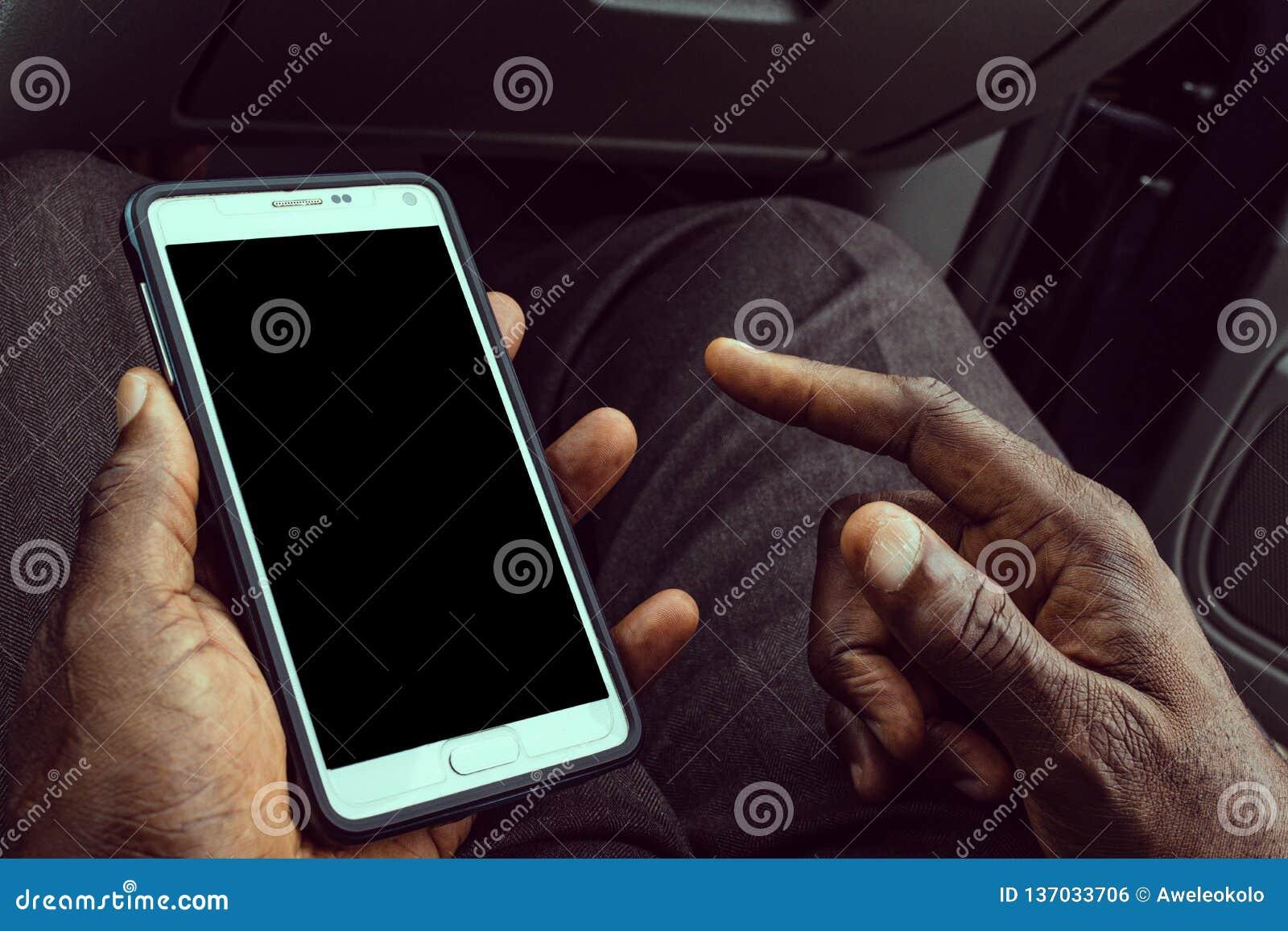 Afroamerikanermann unter Verwendung des intelligenten Mobiltelefons mit leerem schwarzem Schirm Schein oben von einem Holdinggerä