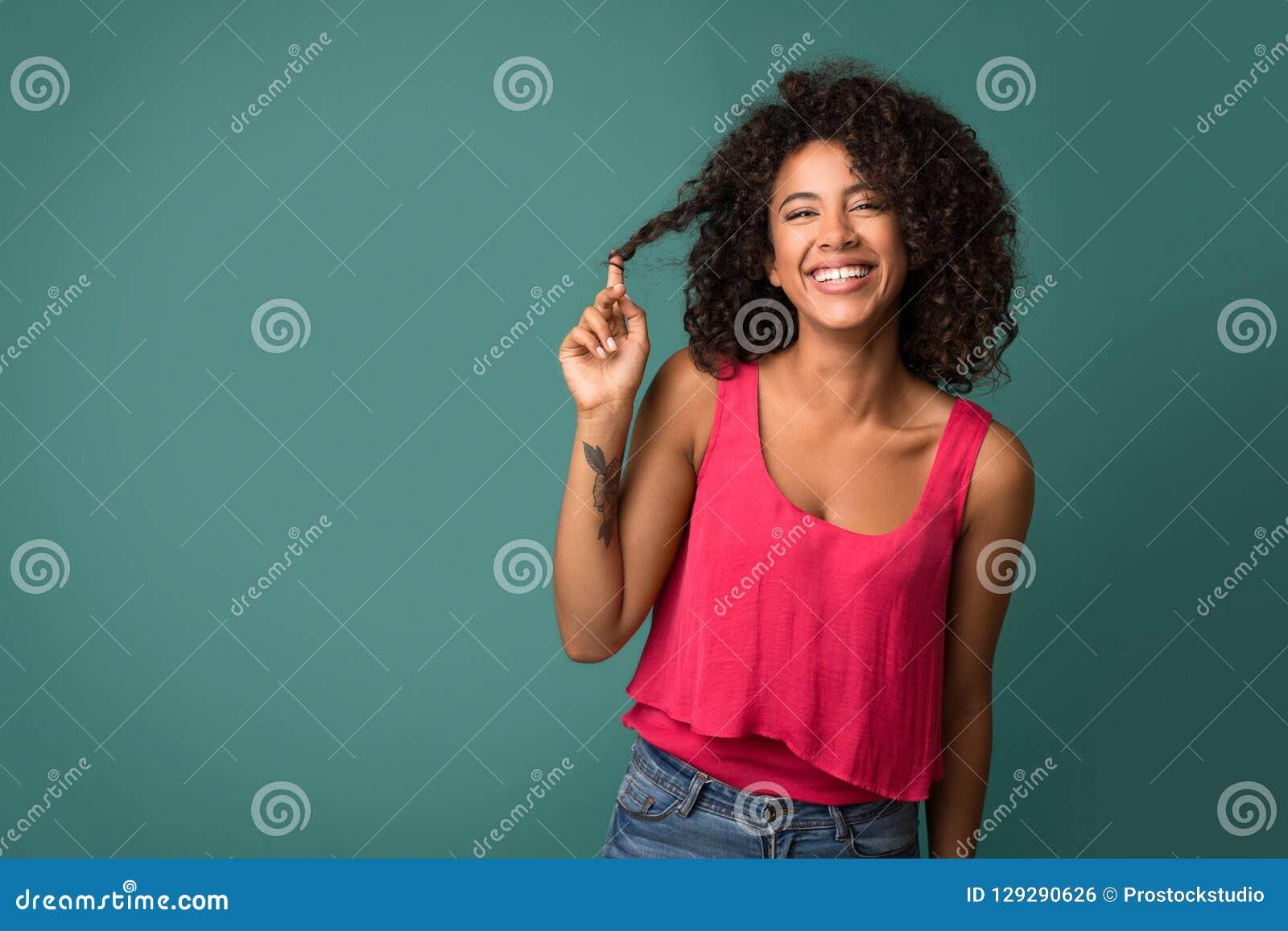 Afroamerykańska kobieta dotyka jej kędzierzawego włosy na turkusowym tle