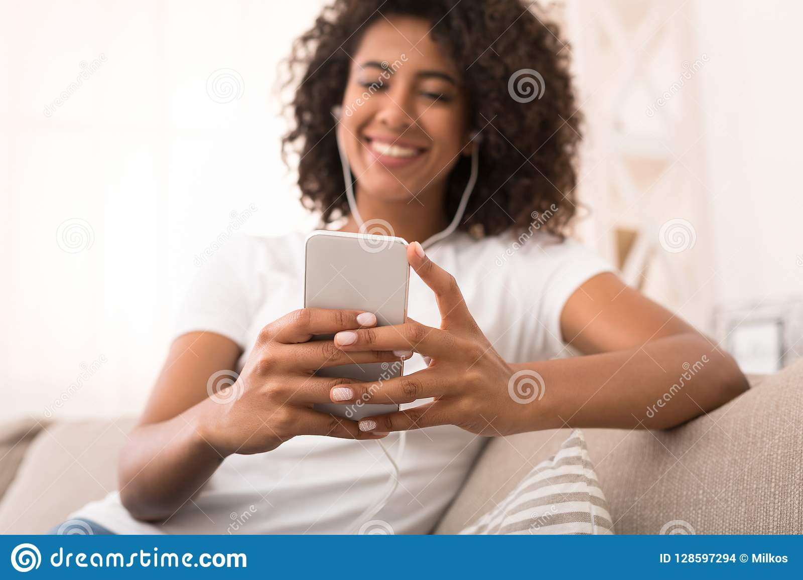 Afroamerykańska kobieta patrzeje telefonu komórkowego pokazu