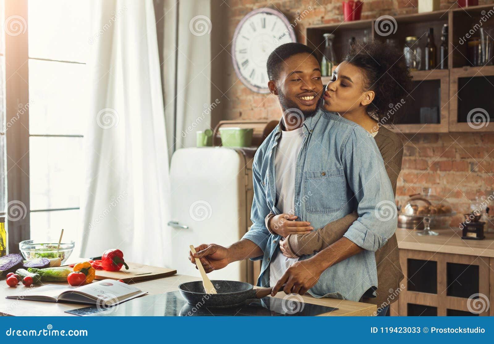 Afroamerykański żony całowania mąż w kuchni
