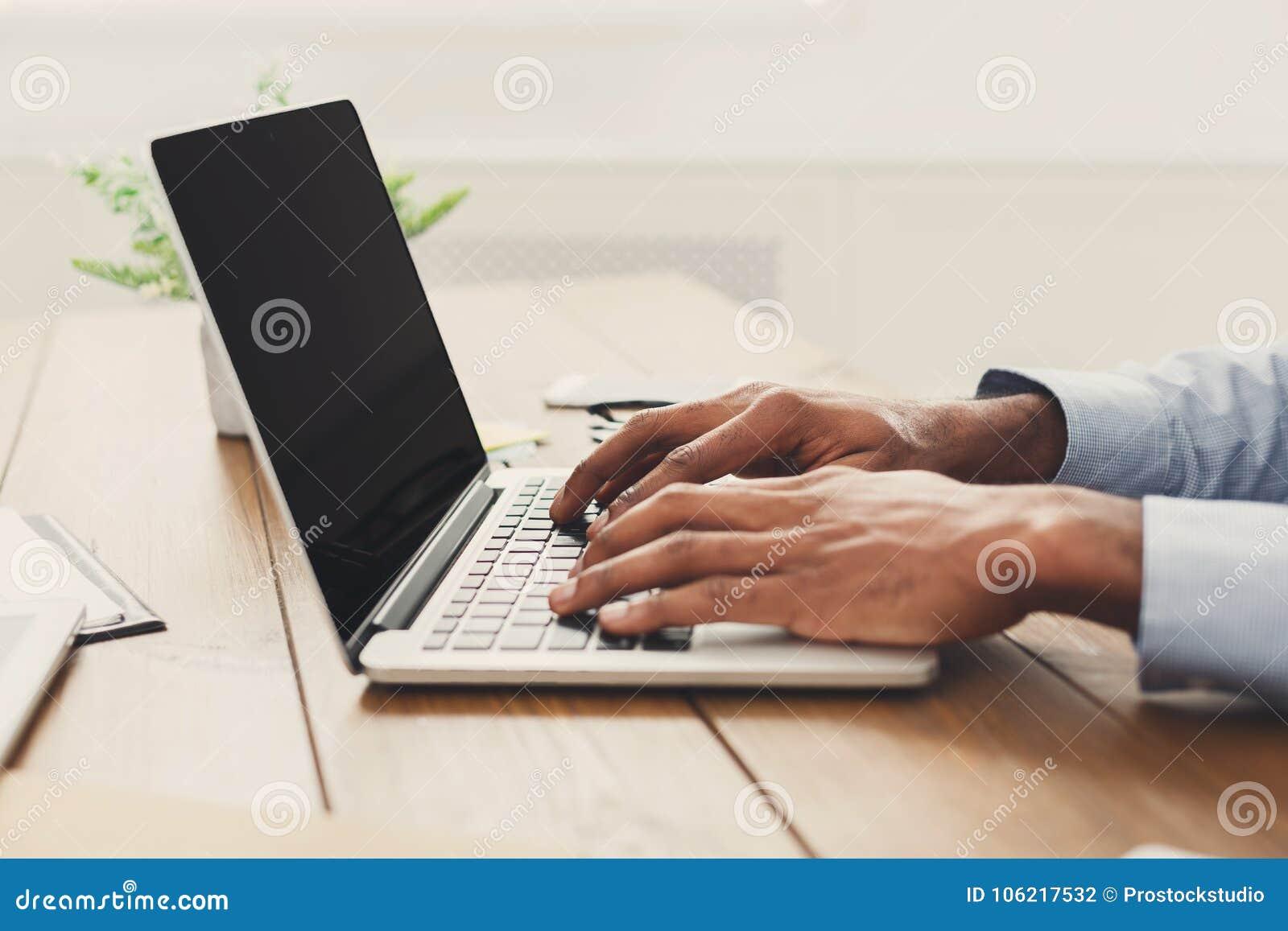 Afroamerykański biznesmen pisać na maszynie na laptopie