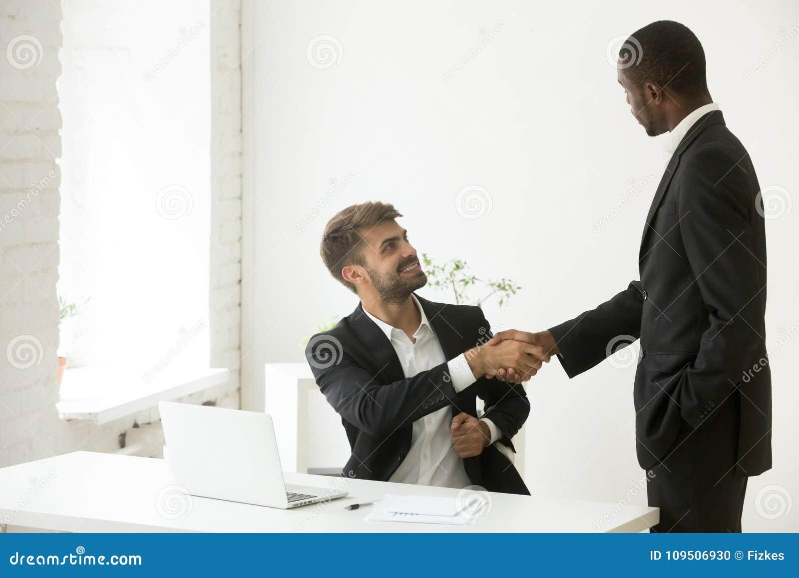 Afroamerykański szef gratuluje caucasian pracownika z pro