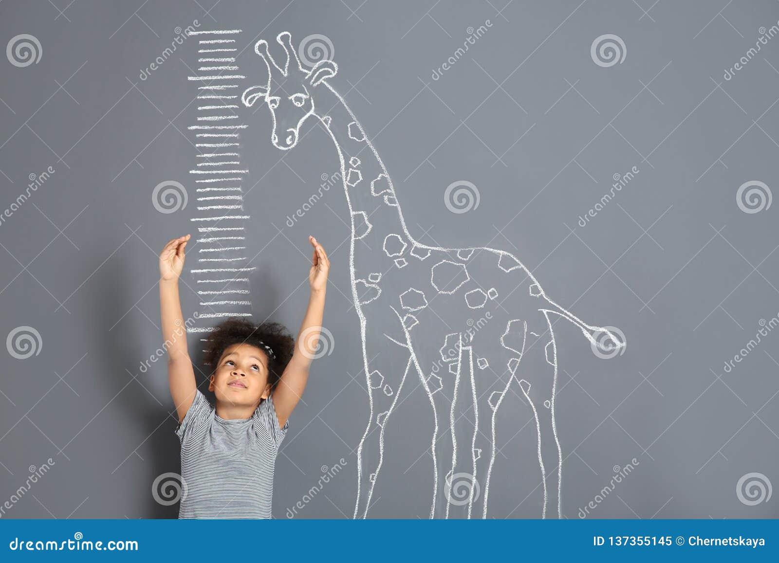 Afroamerykańskiego dziecko pomiarowego wzrosta żyrafy pobliski kredowy rysunek na popielatym