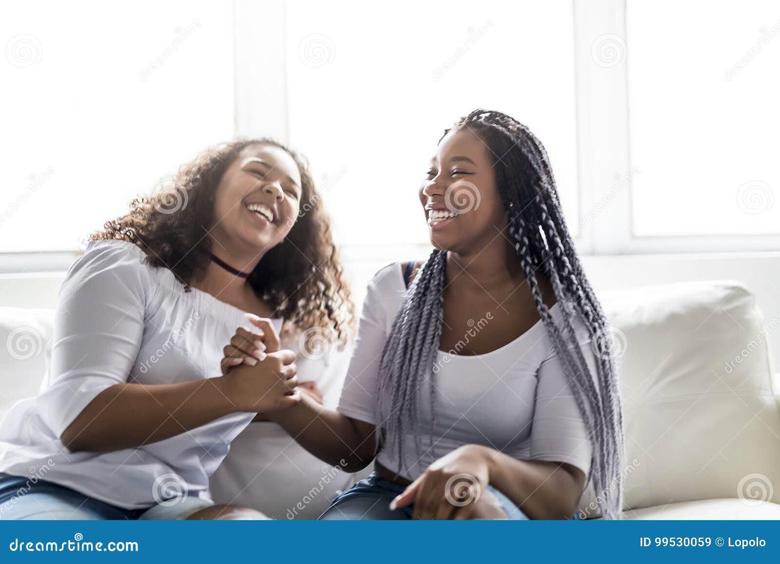 Afroes-amerikanisch Sitzen der liebevollen Freunde auf Sofa