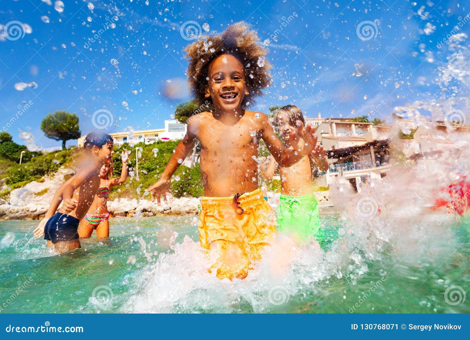 Afrykańska chłopiec bawić się z przyjaciółmi w płytkiej wodzie