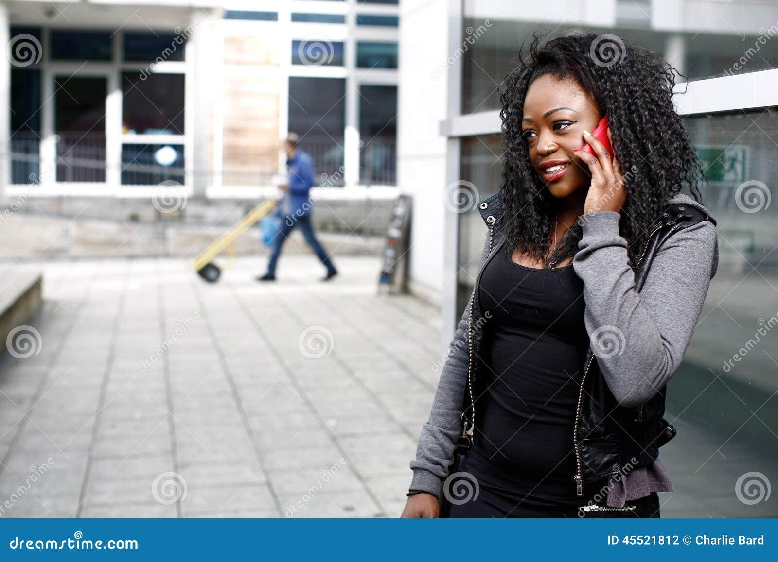 Afrykańska kobieta opowiada na jej wiszącej ozdobie w ulicie