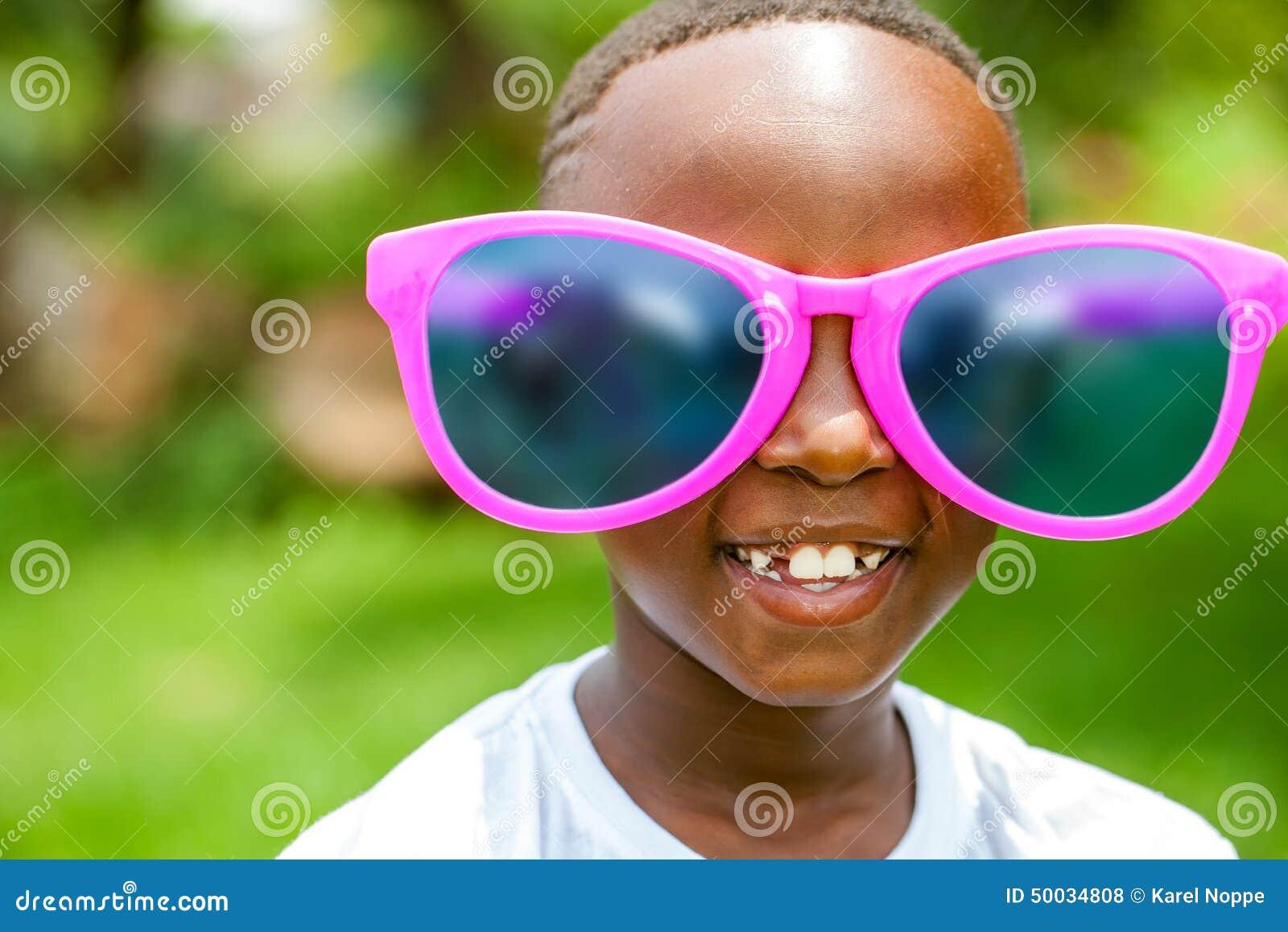 Afrykańska chłopiec jest ubranym zabawy ekstra ampuły słońca szkła