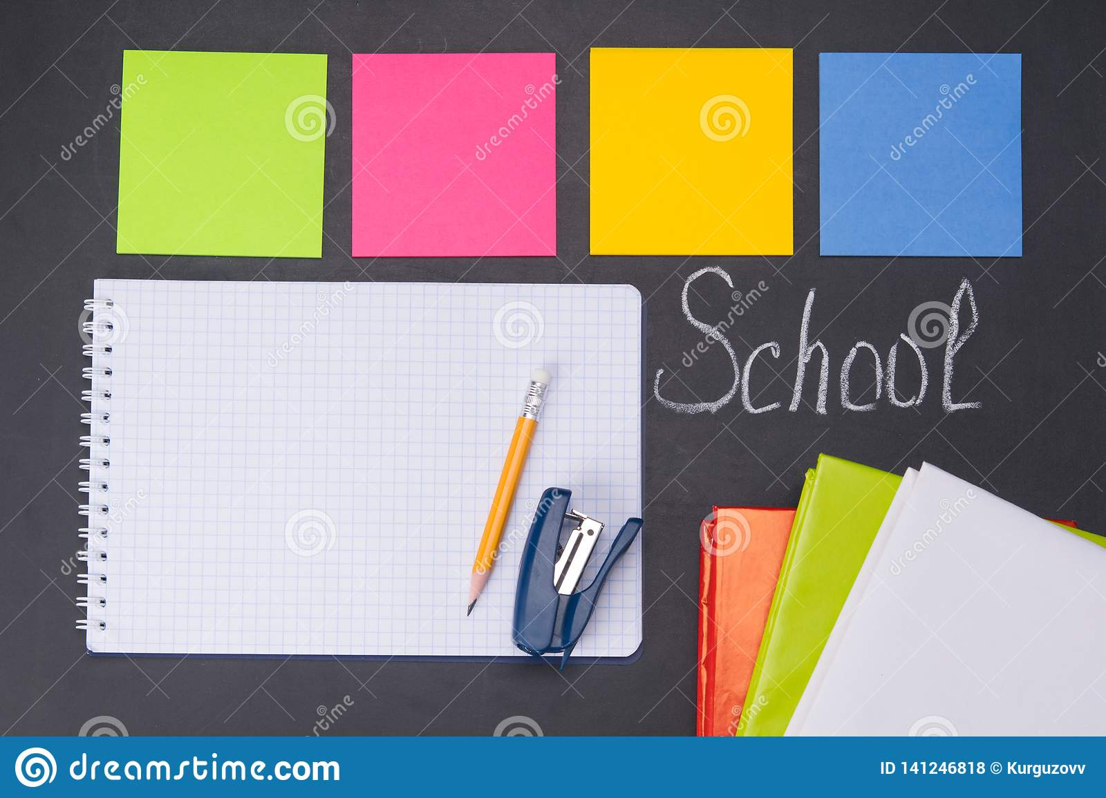 Against the background of a black Board with the inscription school, are subjects for study, colorful stickers, notebook, books,