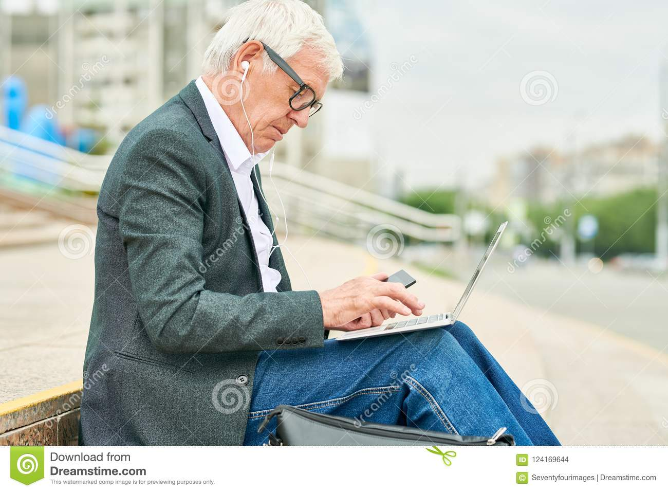Aged businessman using laptop and listening to music