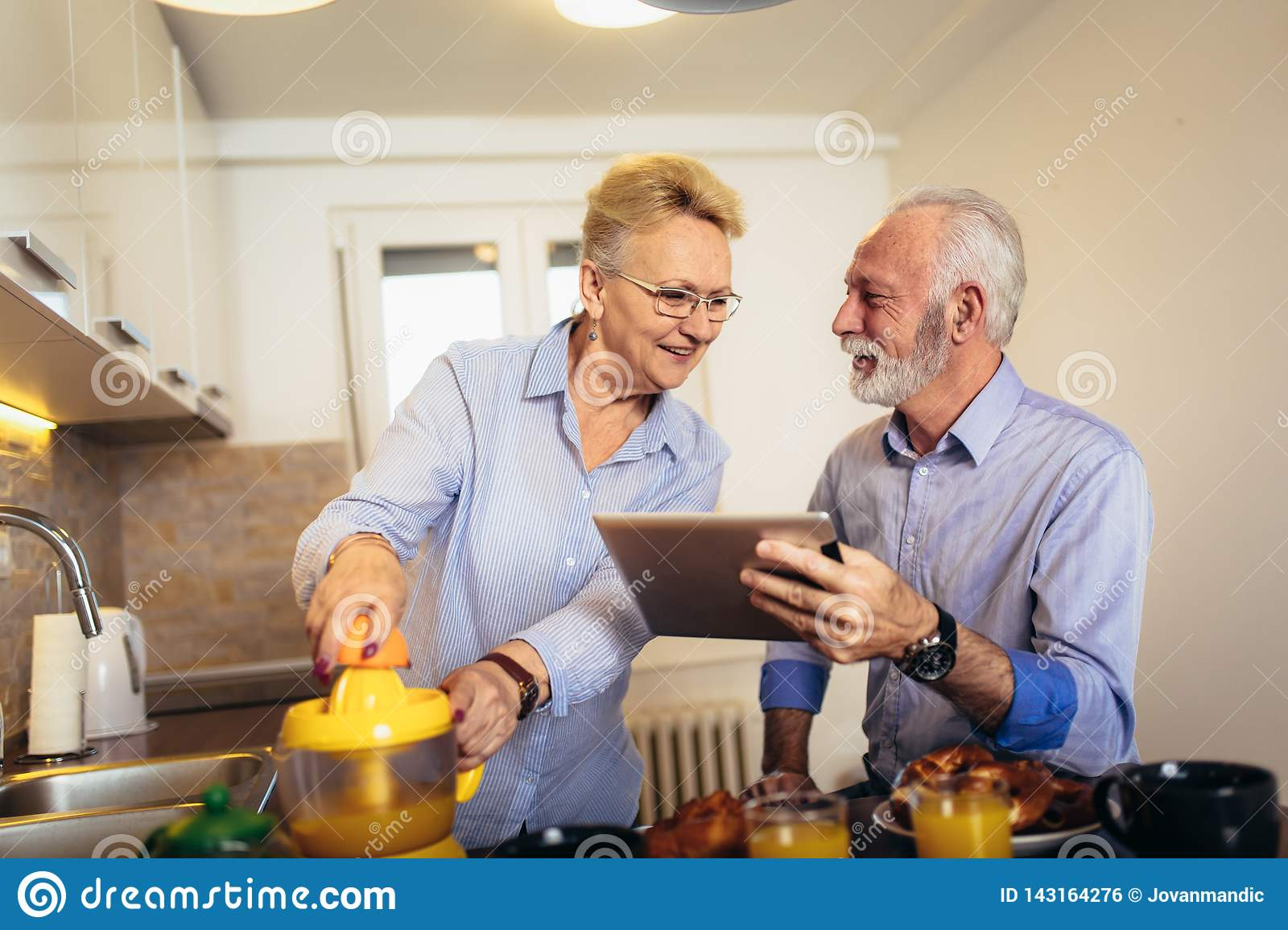 Couple busy look at digital tablet while having delicious breakfast at home kitchen