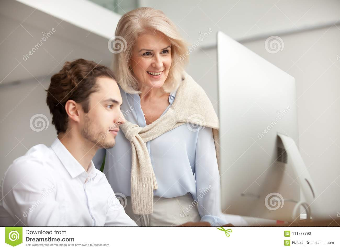 Smiling aged female mentor looking at computer screen helping in