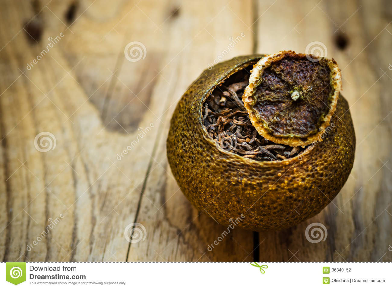 Aged fermented black chinese puer tea in a tangerine peel with lid, weathered wood background, close up
