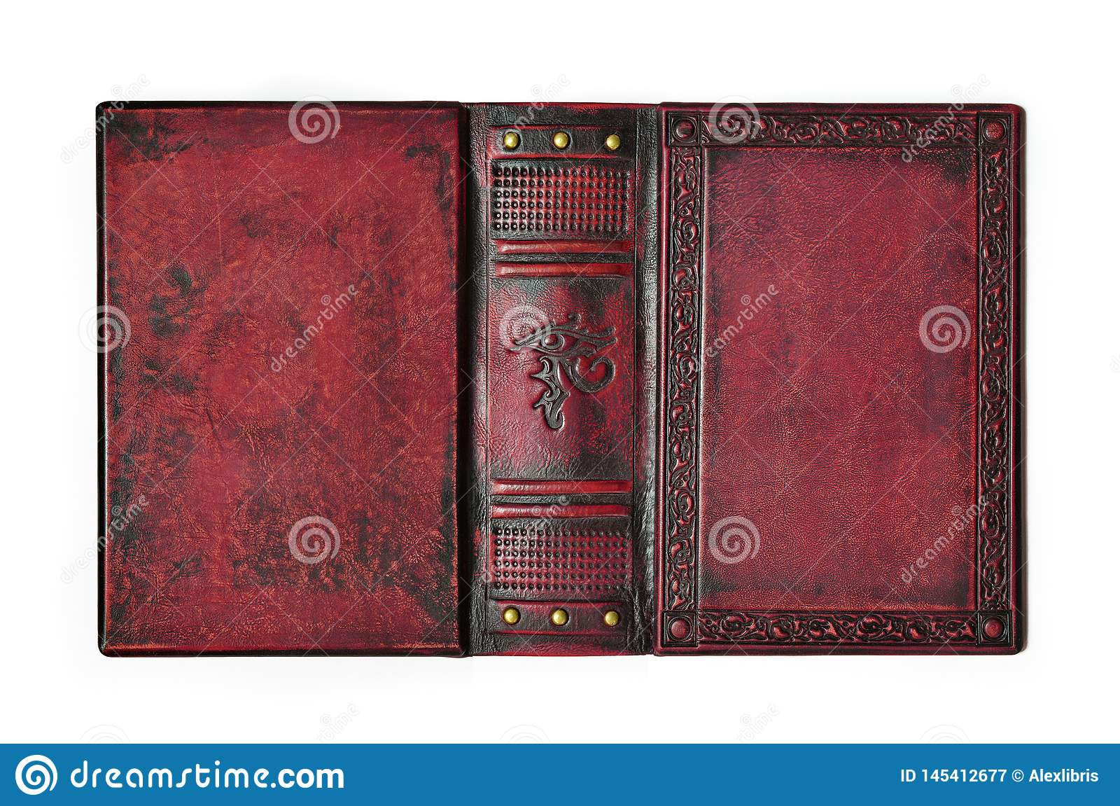 Aged red leather book cover with the embossed ancient Egyptian symbol `The Eye of Horus` lay down to the table opened