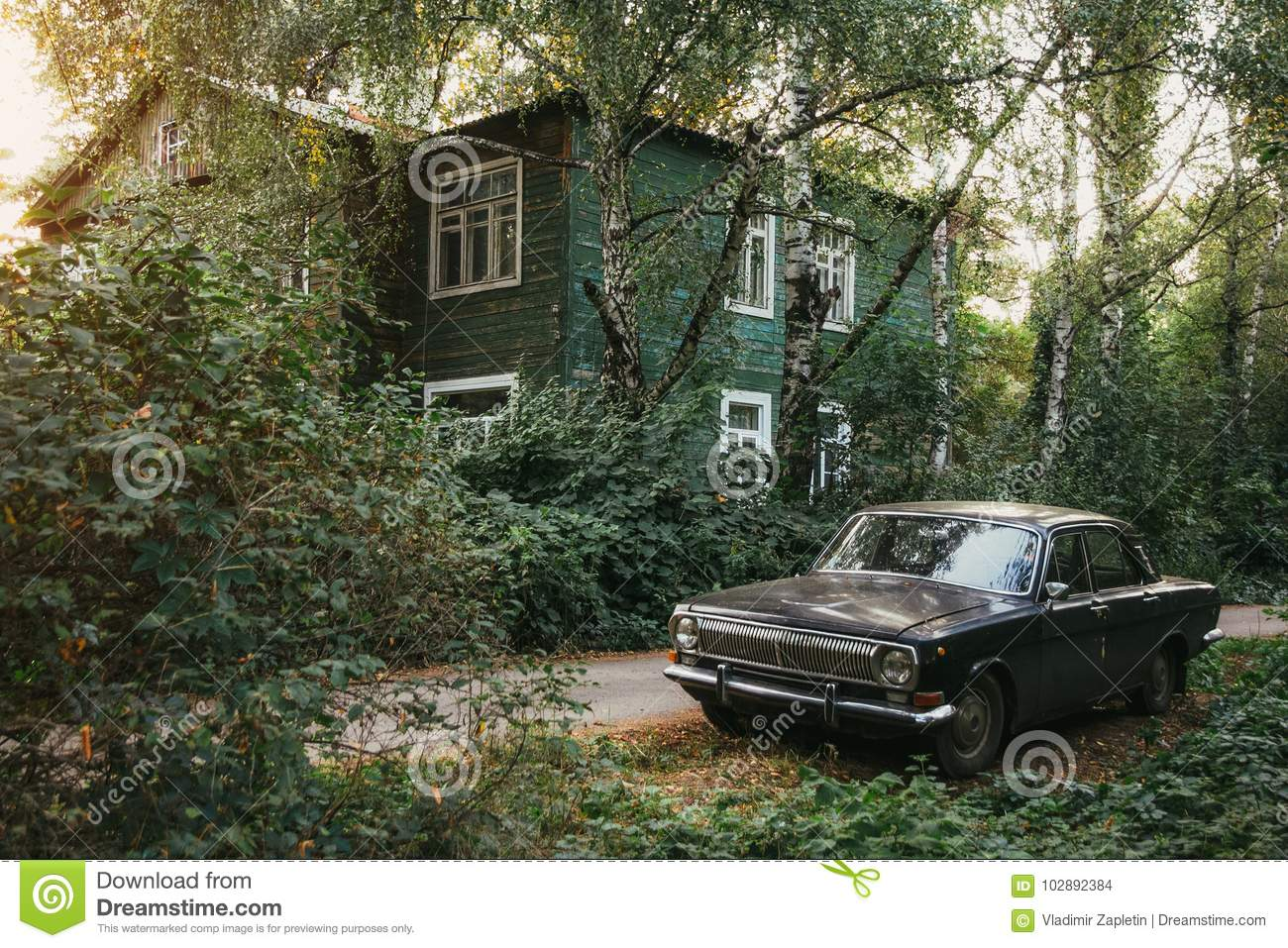 Aged vintage soviet black retro car on background of green wooden old house and autumn park
