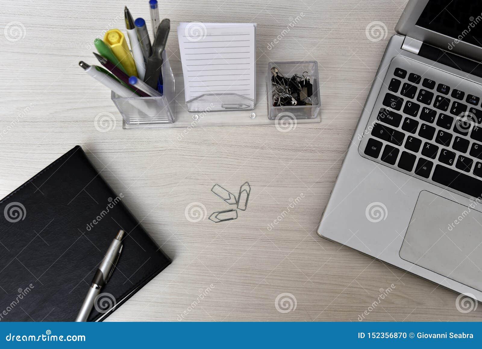 Agenda z biurka i książkowego materiałem na stole