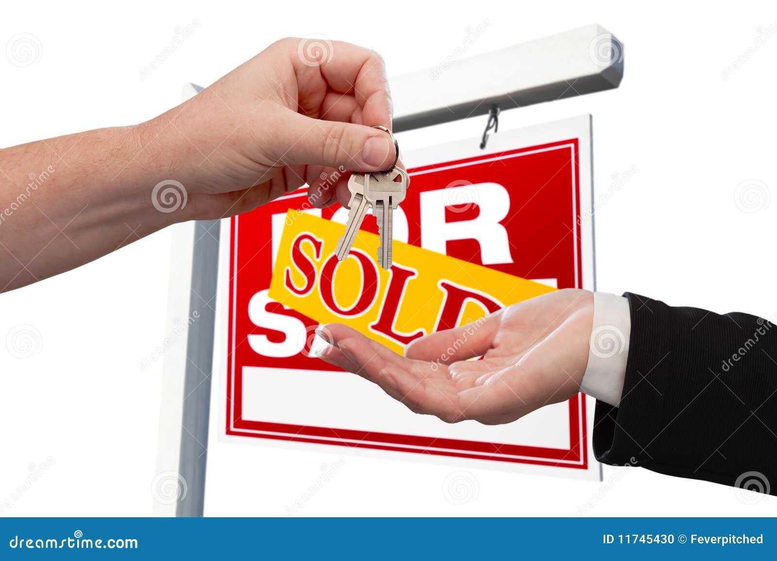 Een Nieuw Huis : Agent die de sleutel overhandigt aan een nieuw huis stock foto