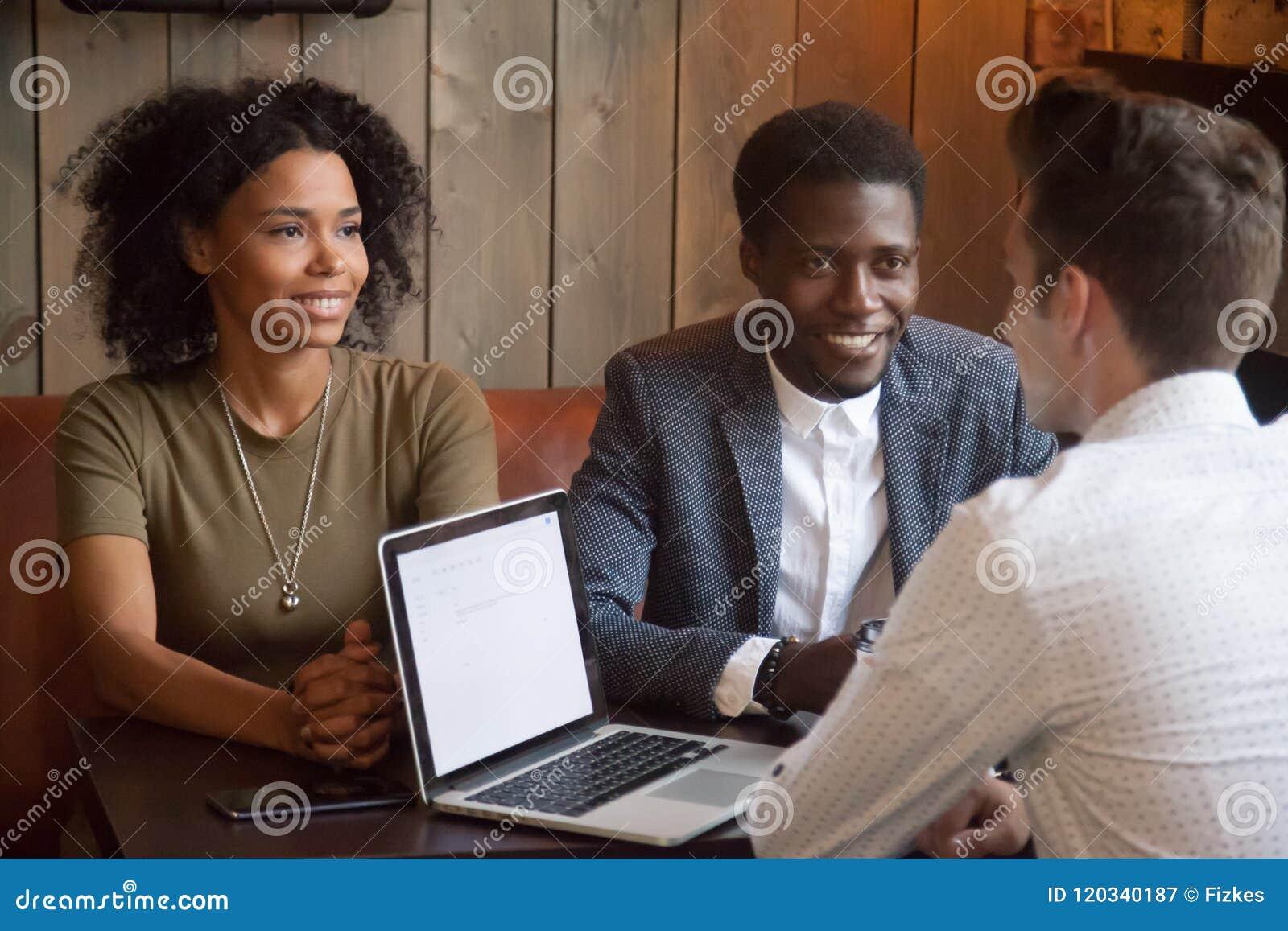 Agent immobilier caucasien consultant les clients noirs lors de la réunion de café
