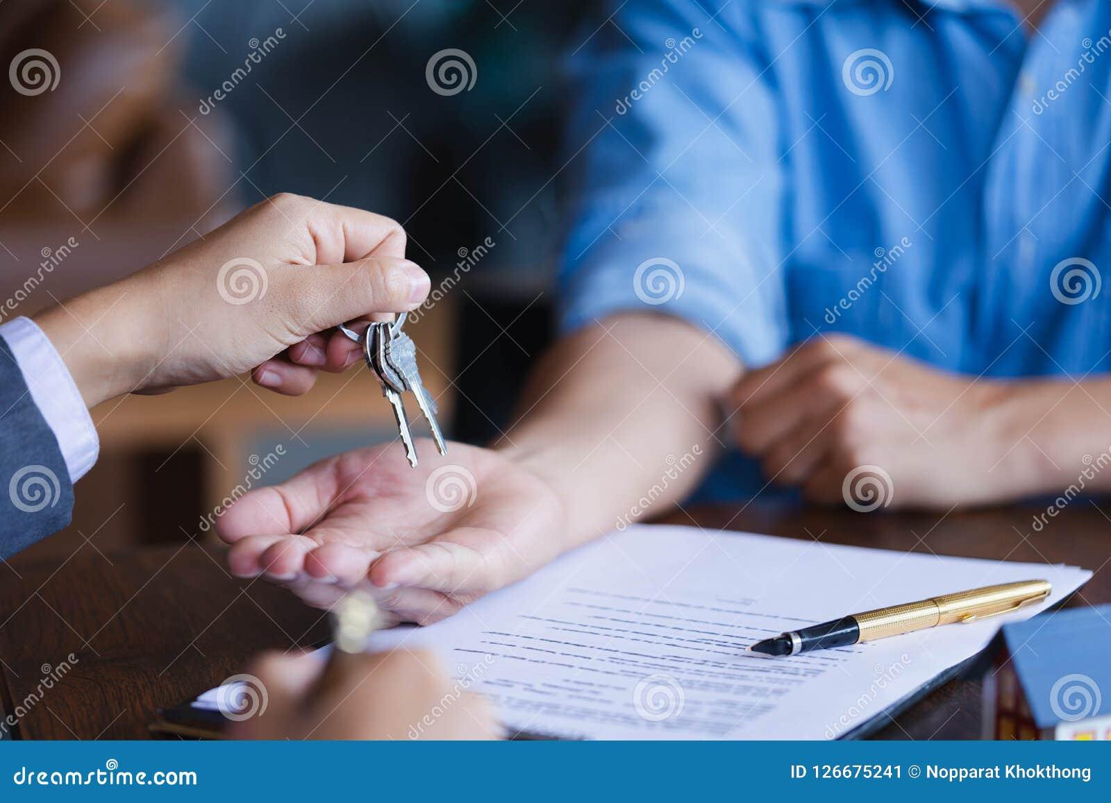 Agent immobilier donnant des clés à de nouveaux propriétaires après signi