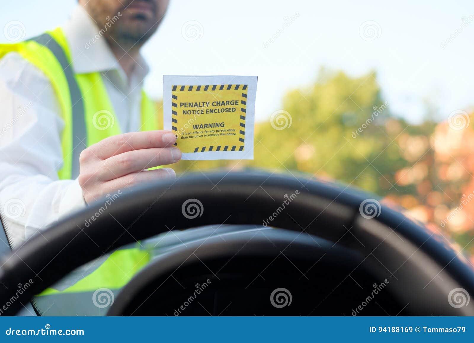 Agente da polícia que dá uma multa para a violação de estacionamento