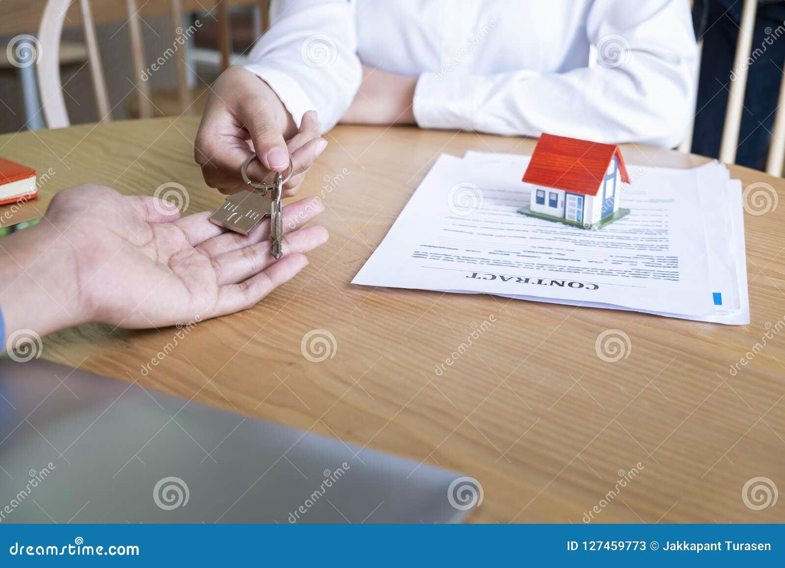 Agente de la propiedad inmobiliaria que da llaves de la casa al acuerdo del dueño y de la muestra en oficina